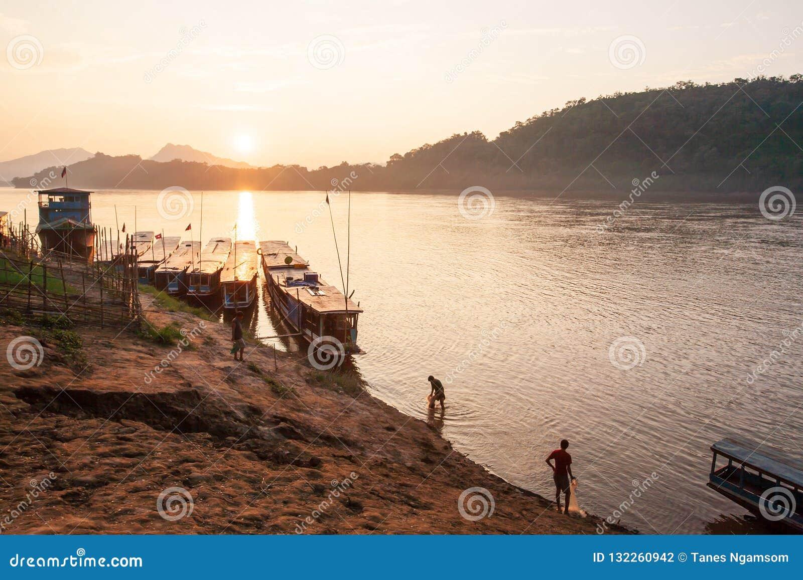 Två fiskare med fisknät i Mekonget River på solnedgången S