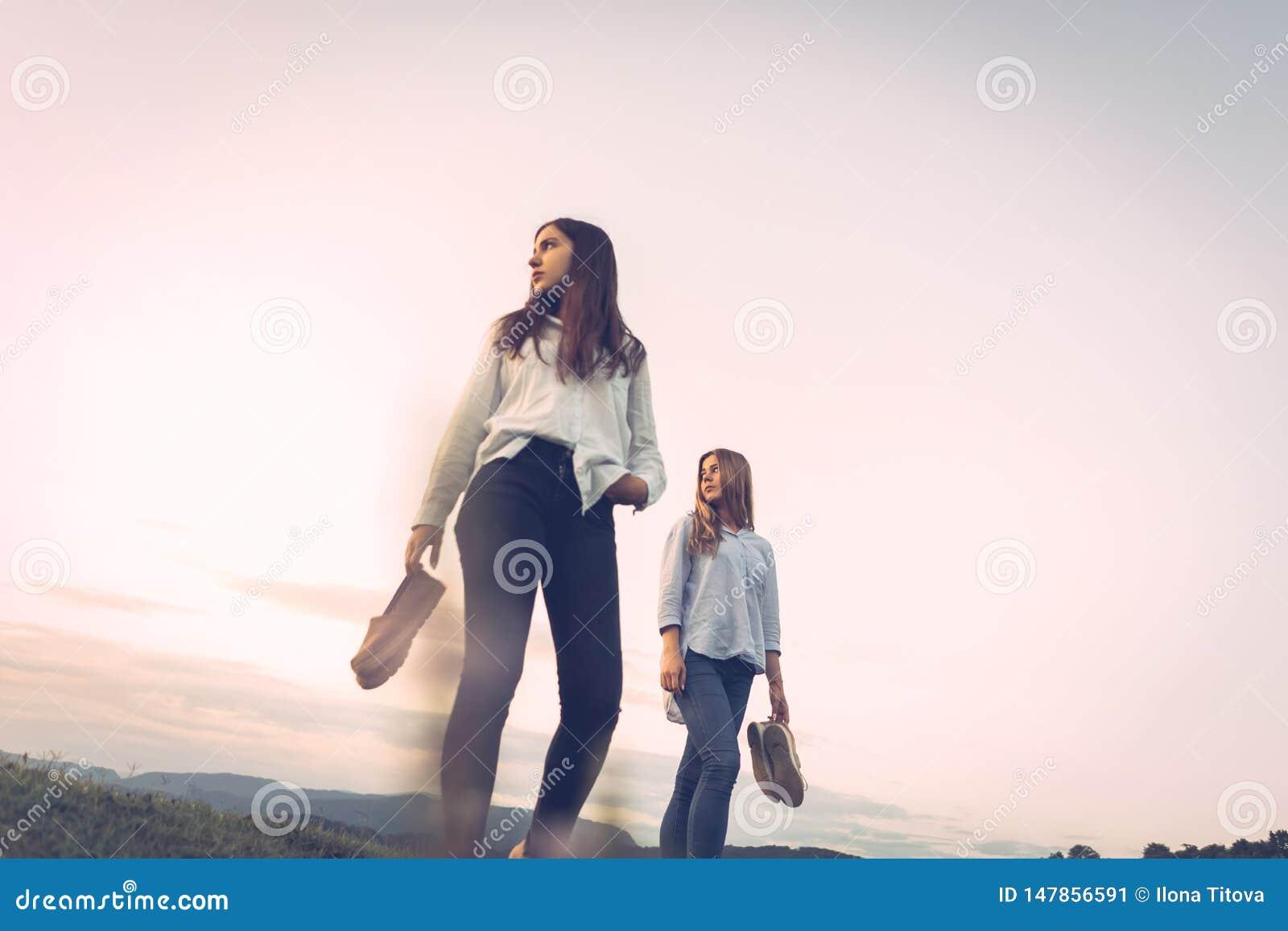 Två flickor från en lägre vinkel med skor i deras händer