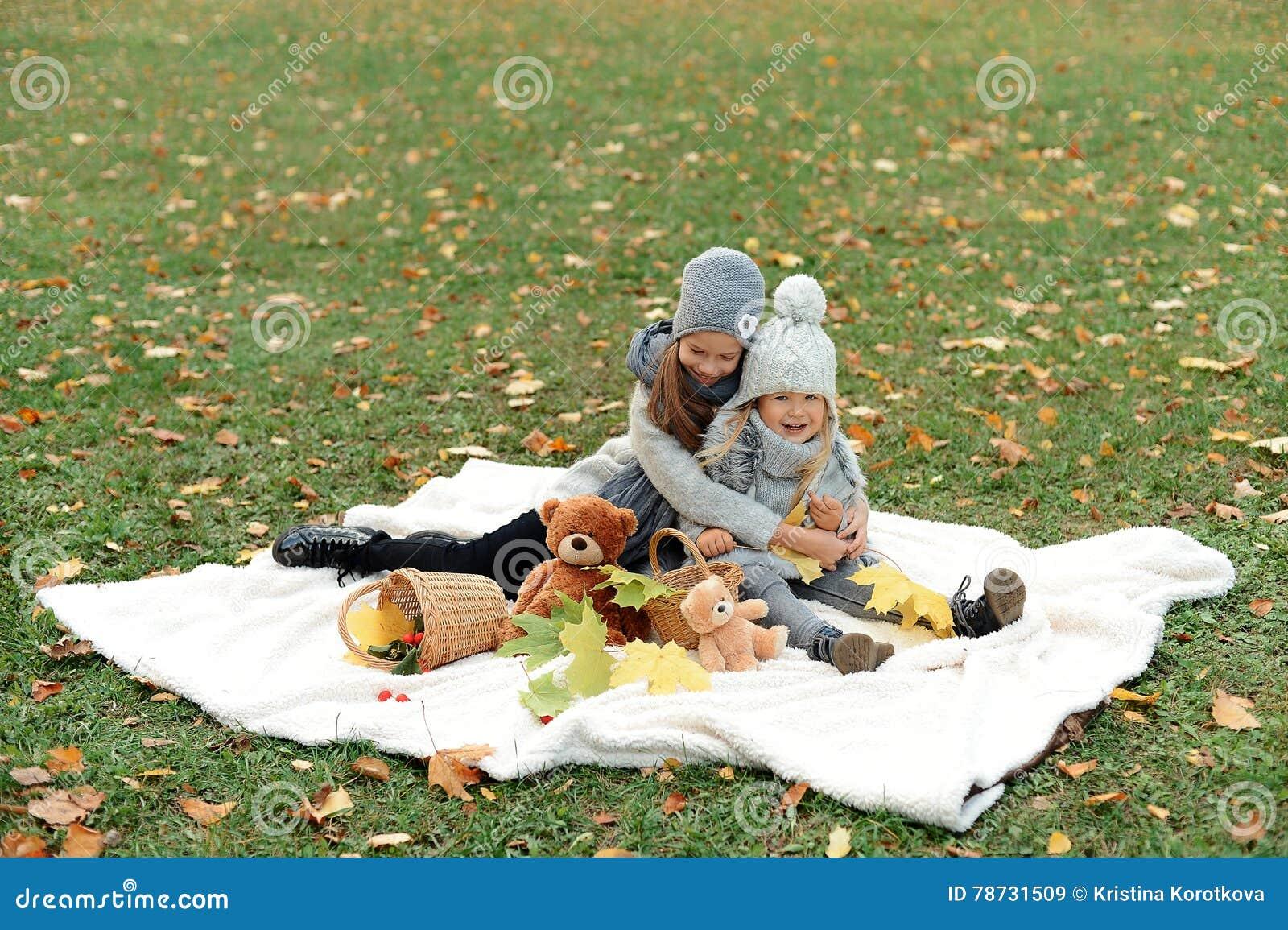 Två flickor i gråa lock ordnar en picknick i höst parkerar i aftonen