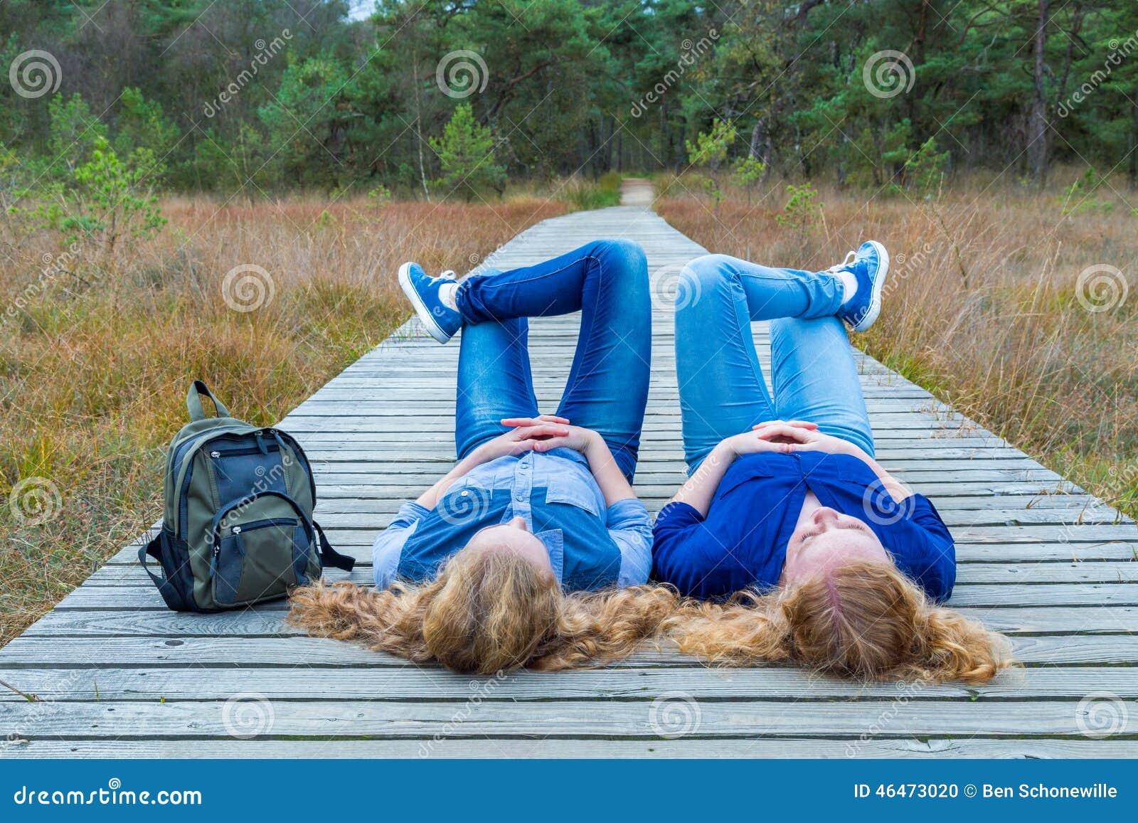 Två flickor som ligger på deras baksidor på träbanan i natur