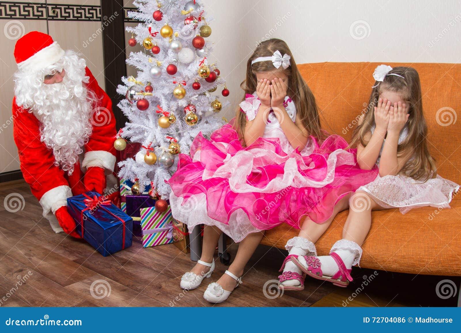 Två flickor stängde ögon med hans händer, tills Santa Claus satte gåvor under julgranen
