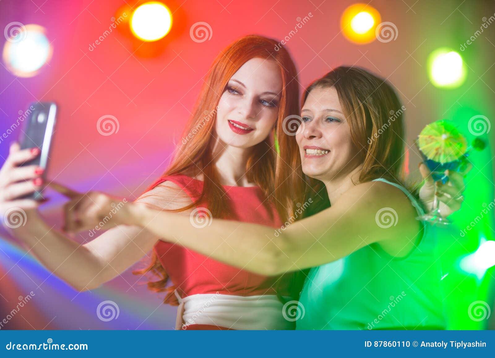 Två flickvänner i en nattklubb under strålkastaren