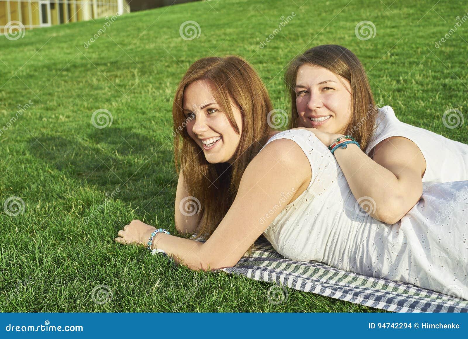 Två flickvänner som ligger på gräsmattan