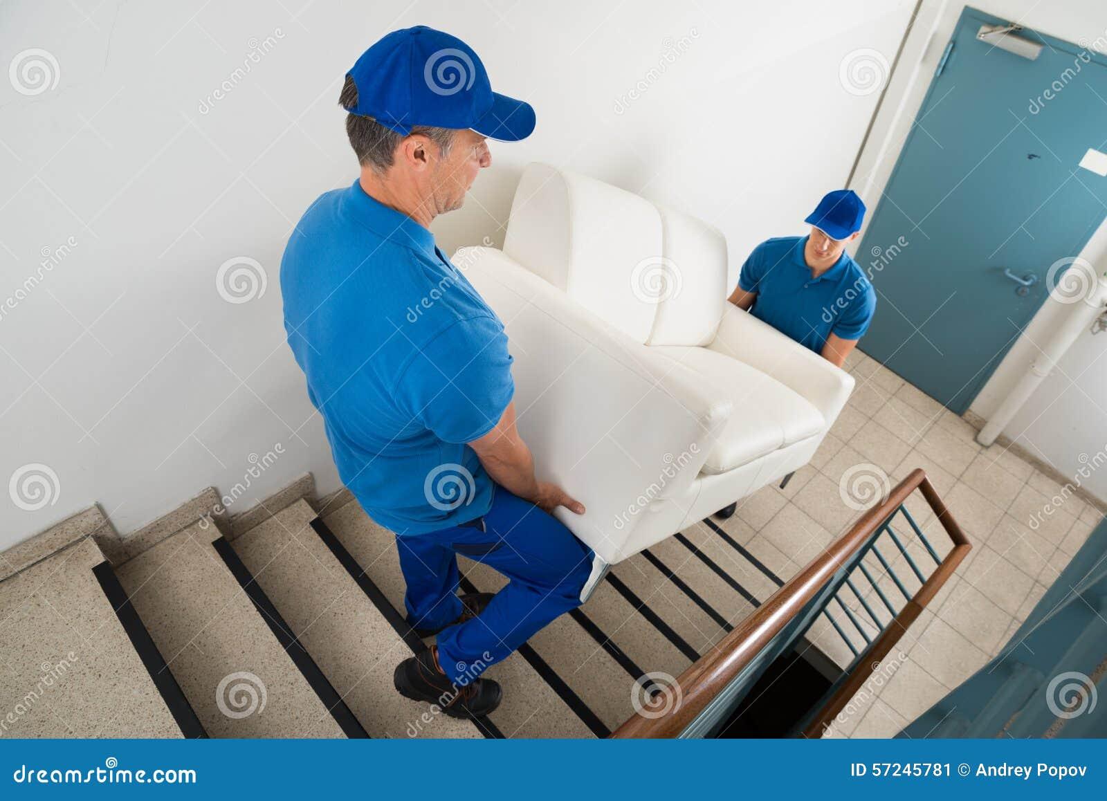 Två flyttkarlar som bär Sofa On Staircase