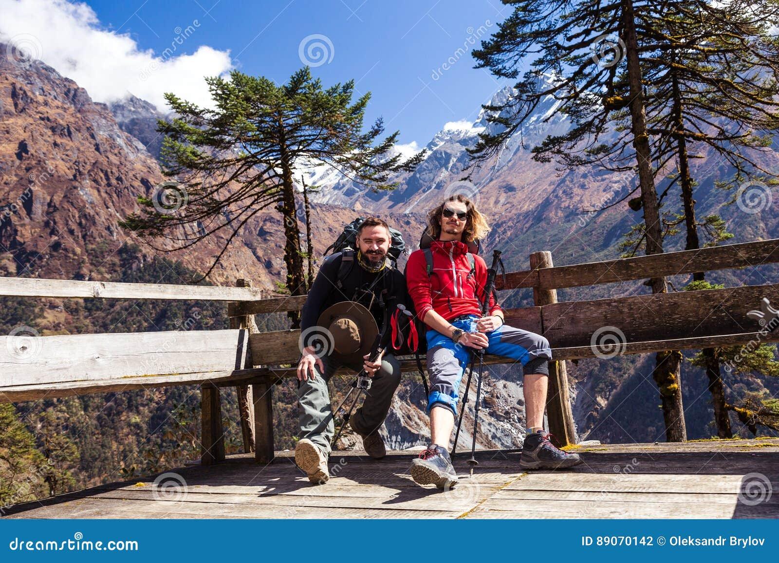 Två fotvandrare som vilar på bergskyddsammanträde på den Wood bänken