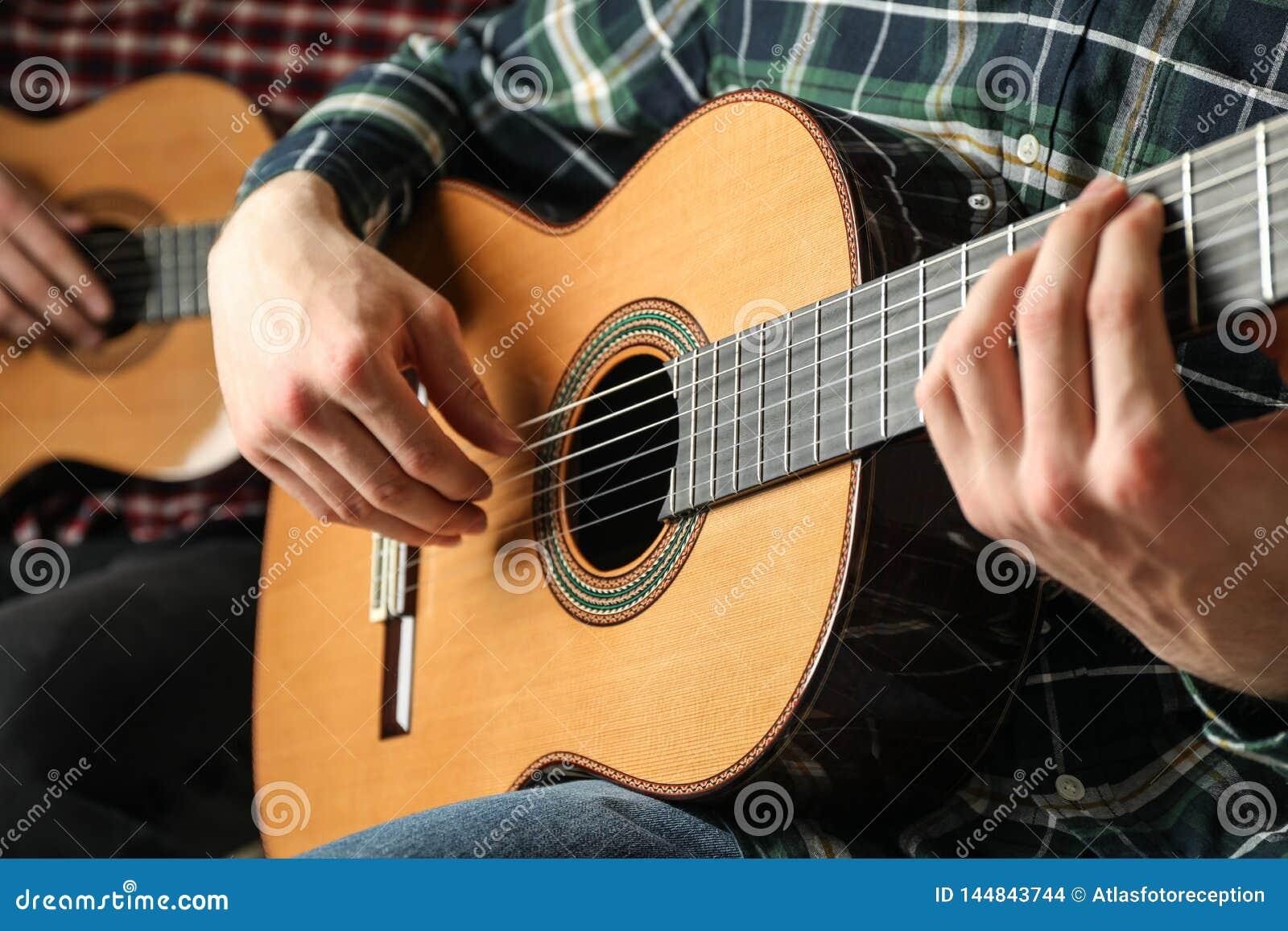 Två gitarrspelare med klassiska gitarrer
