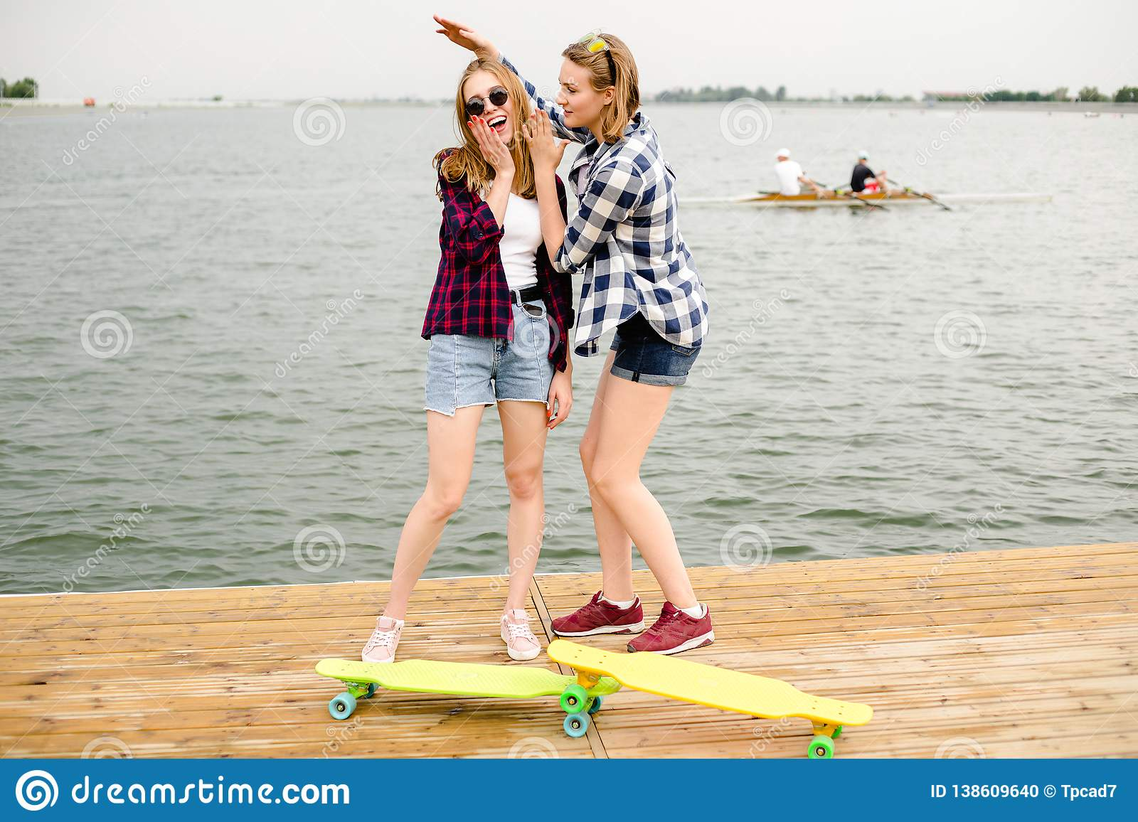 Två gladlynta lyckliga skateboradåkareflickor i hipsterdräkten som har gyckel på en träpir under sommarsemester