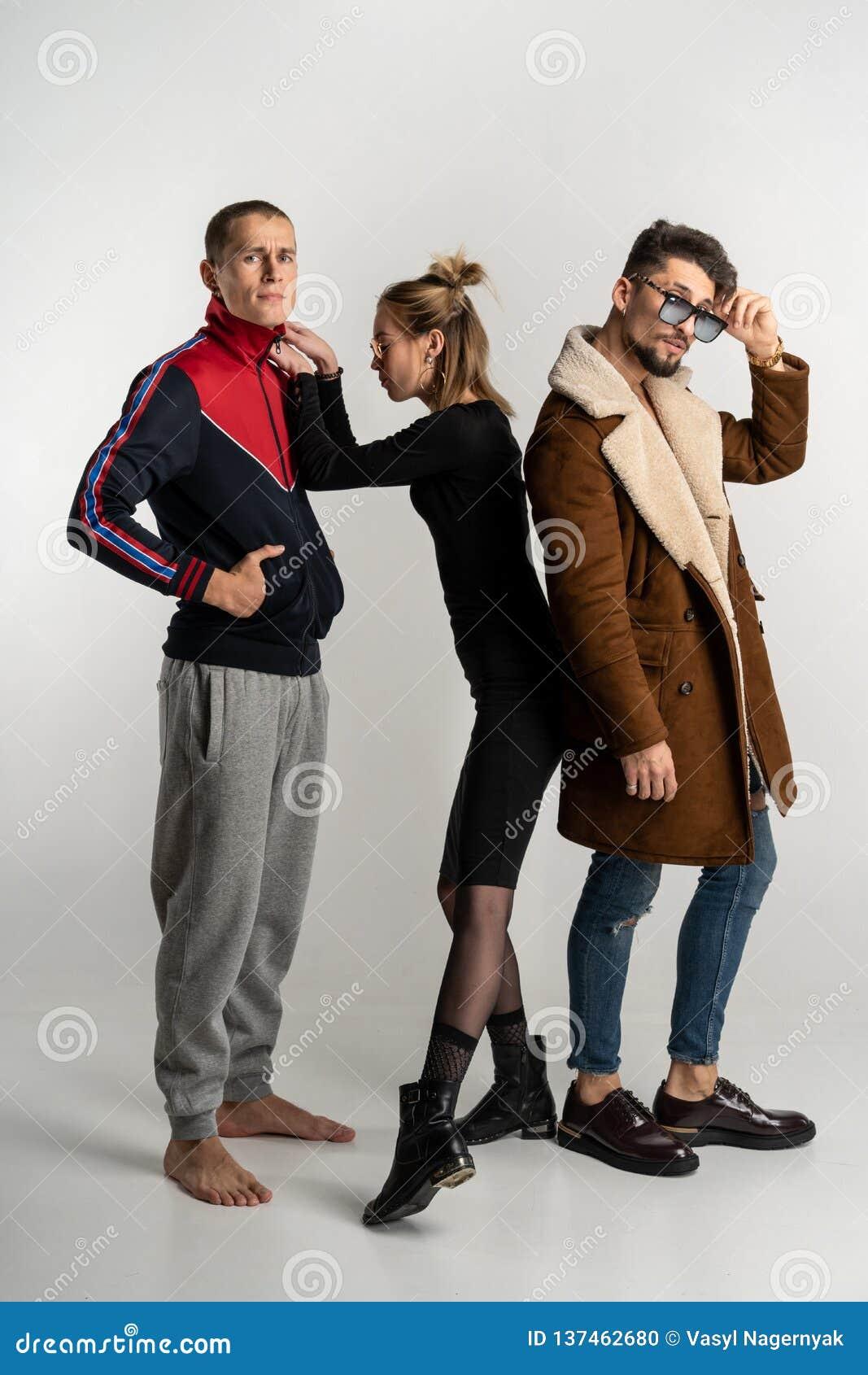 Två grabbar och flicka i stilfull tillfällig ljus och mörk färgrik kläder