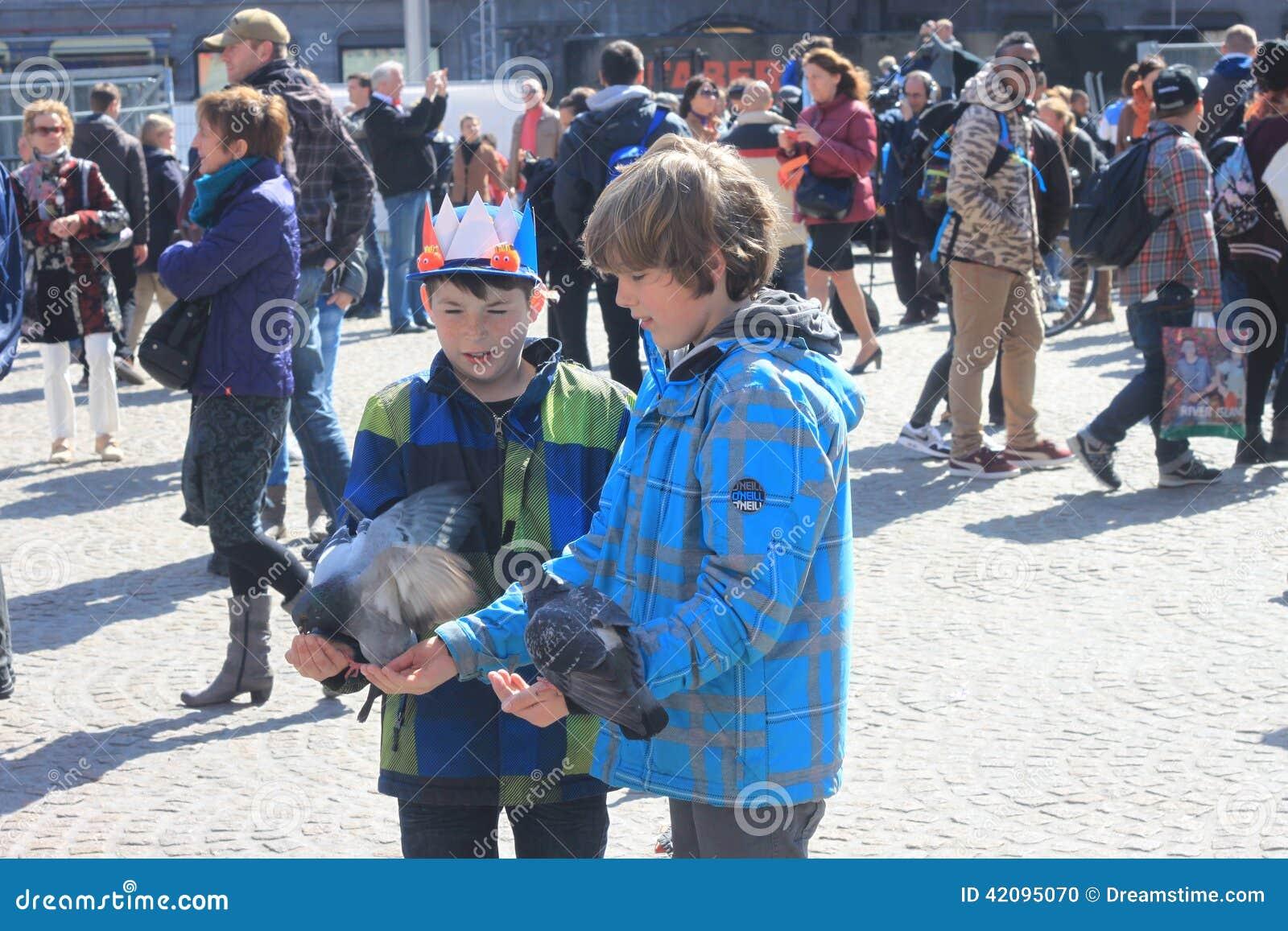 Två grabbar som ger matande duvor fördämningen i Amsterdam