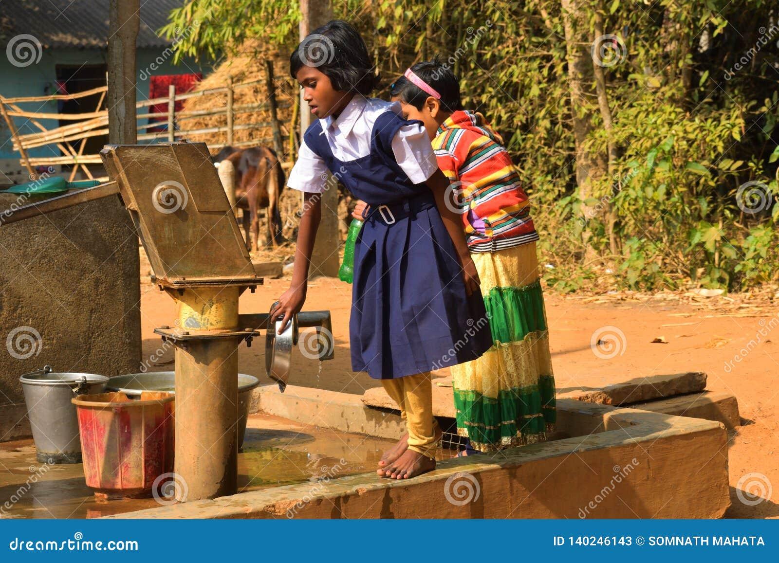 Två grundskola för barn mellan 5 och 11 årflickor tvättar deras hand och deras disk, innan de tar Mitt--dagen mål i en grundskola