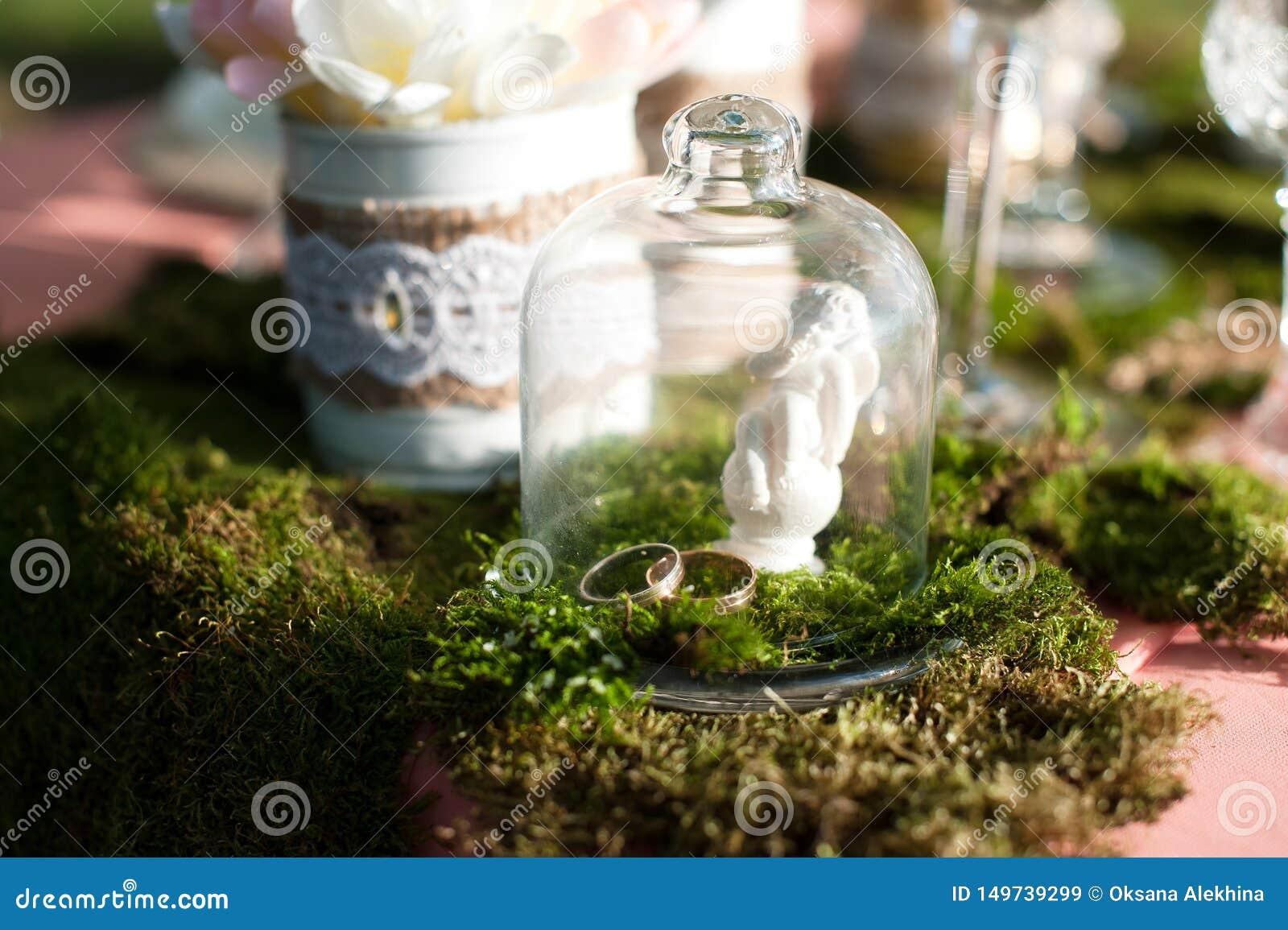 Två guld- vigselringar på en tabell under ett exponeringsglas av exponeringsglas N?rbild