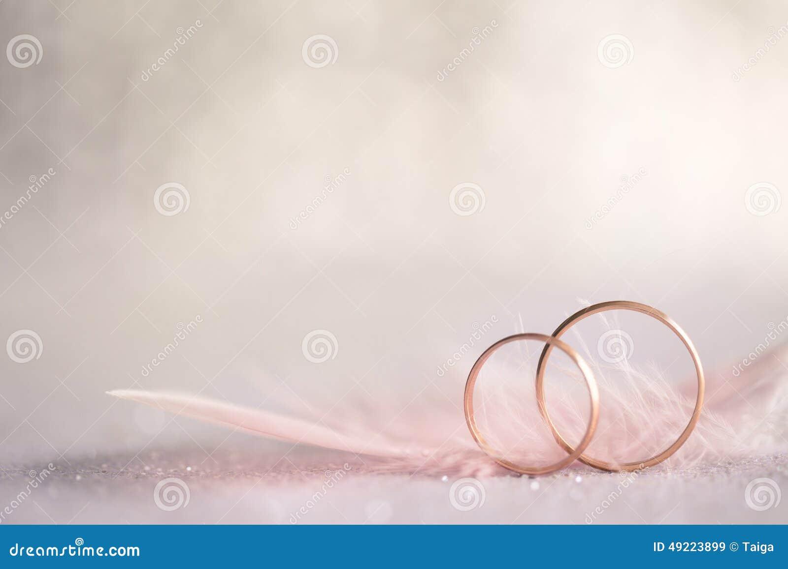 Två guldbröllopcirklar och fjäder - försiktig bakgrund