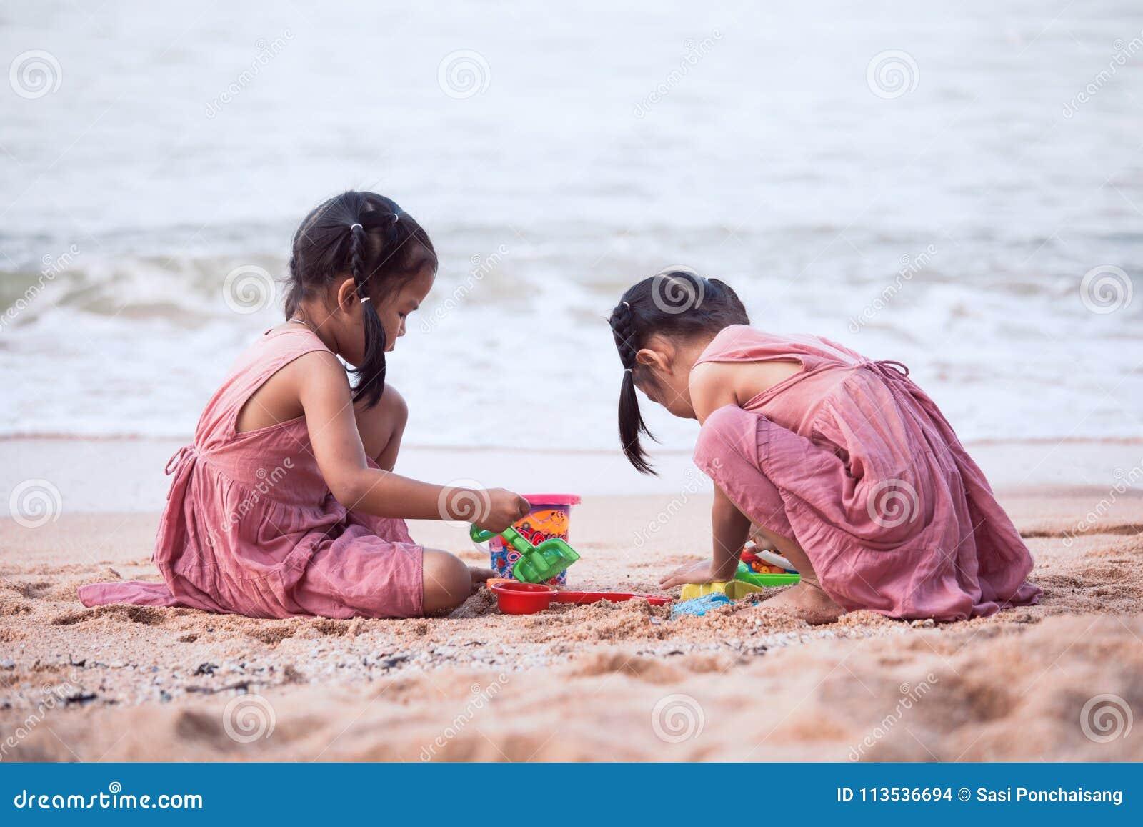 Två gulliga asiatiska flickor för litet barn som har gyckel som spelar med sand