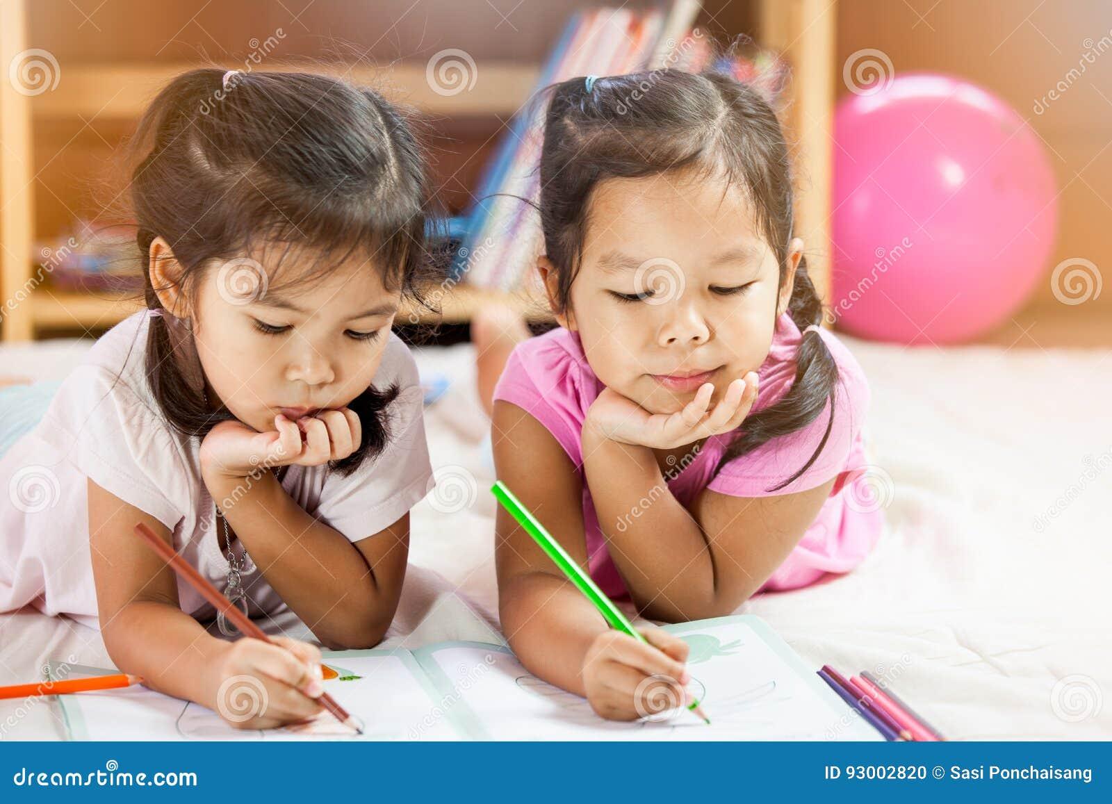 Två gulliga asiatiska små flickor vilar deras haka på deras händer