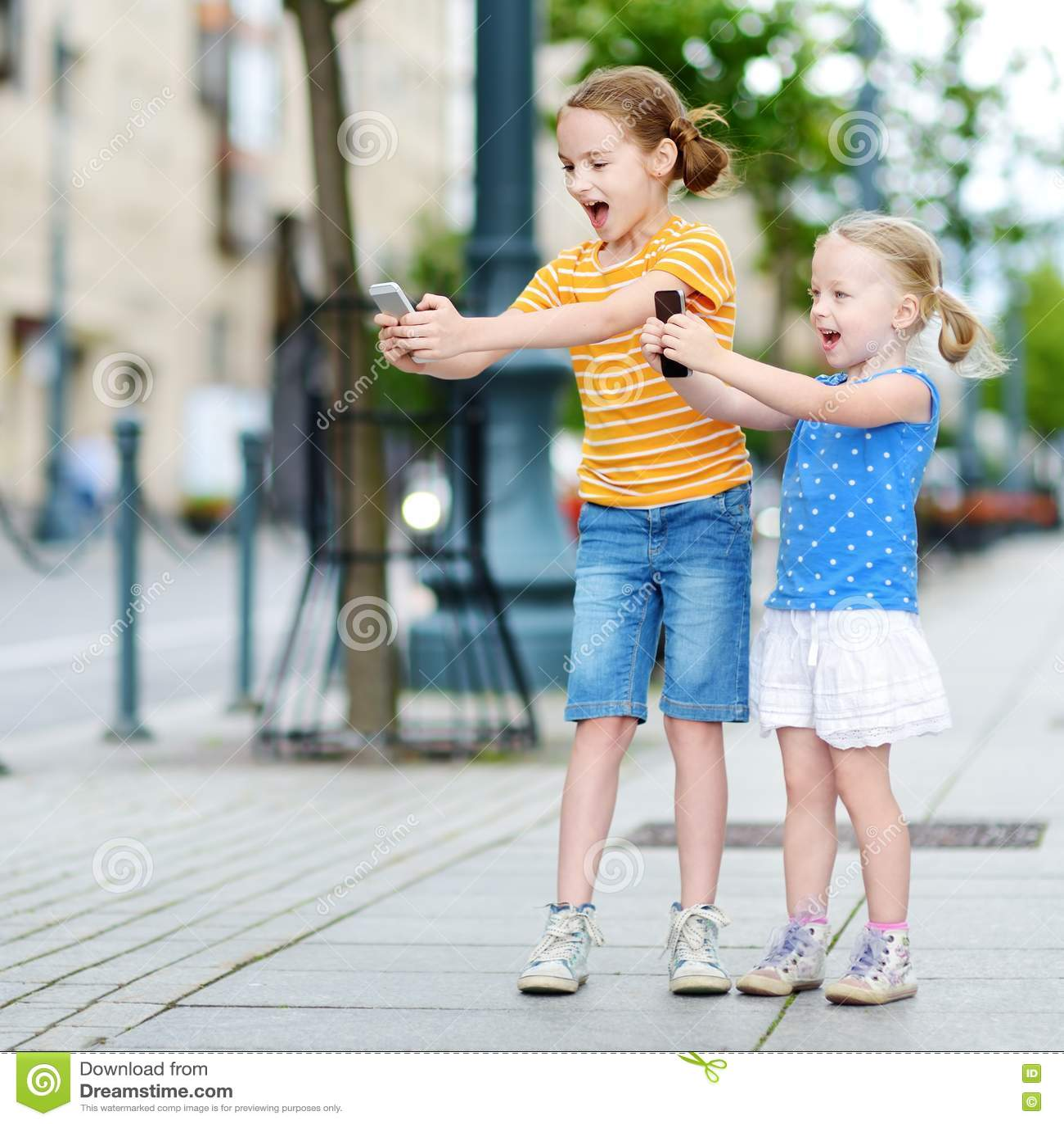 Två gulliga lilla systrar som spelar den utomhus- mobilleken på deras smarta  telefoner 1c66afe757a7a