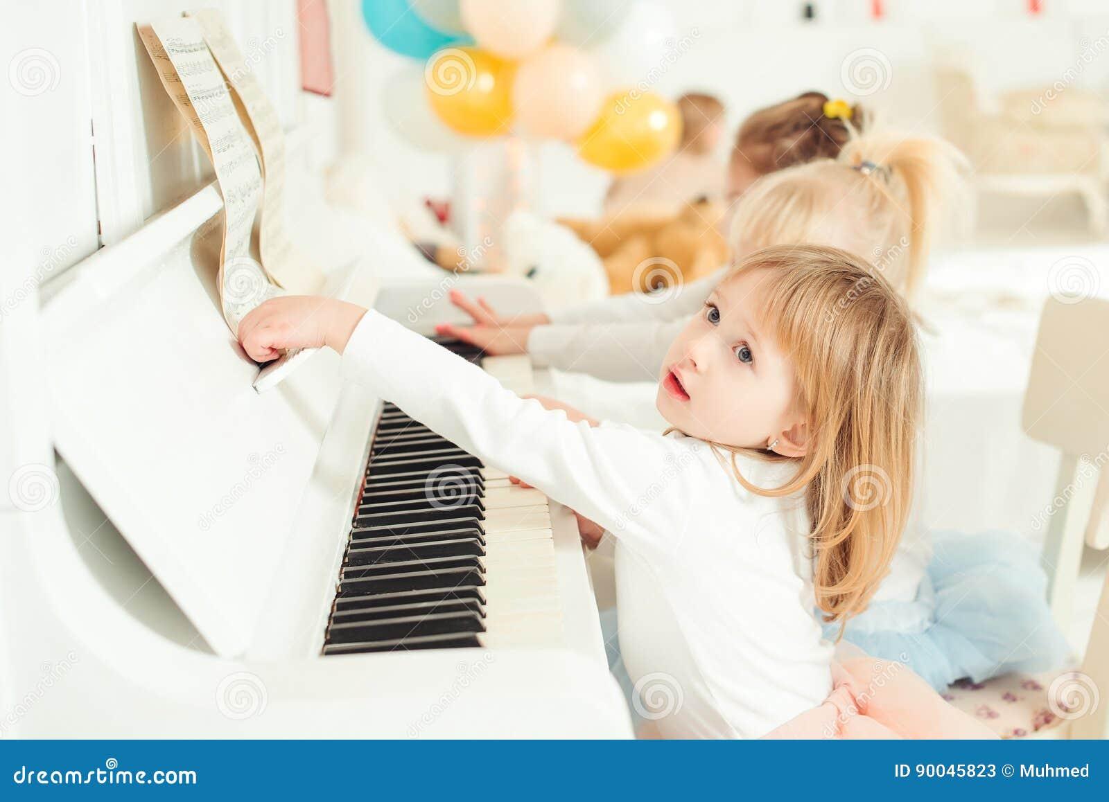 Två gulliga små flickor som spelar pianot i en studio