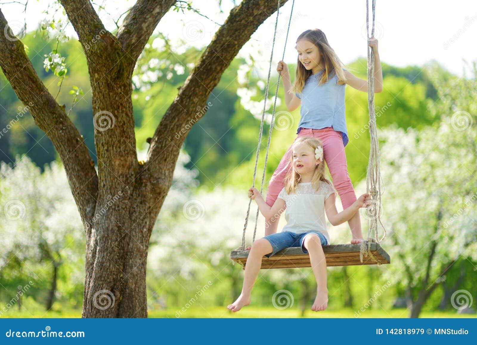 Två gulliga systrar som har gyckel på en gunga, i att blomstra den gamla trädgården för äppleträd utomhus på solig vårdag
