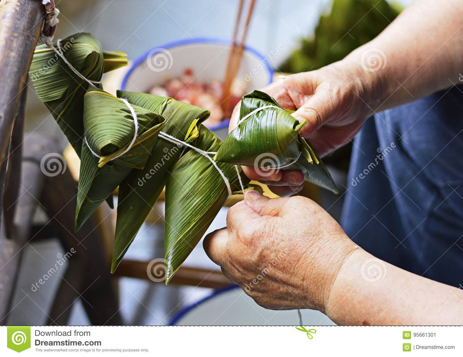 Två händer drar åt raden över bladet för att göra Zongzi, risklimpar för traditionell kines för Dragon Boat Festival