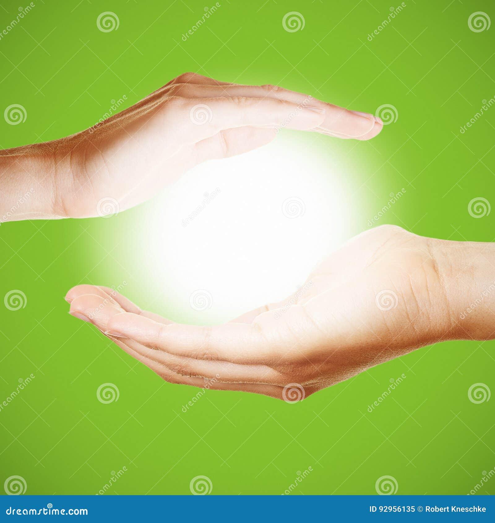 Två händer rymmer ett glödande ljus eller sol
