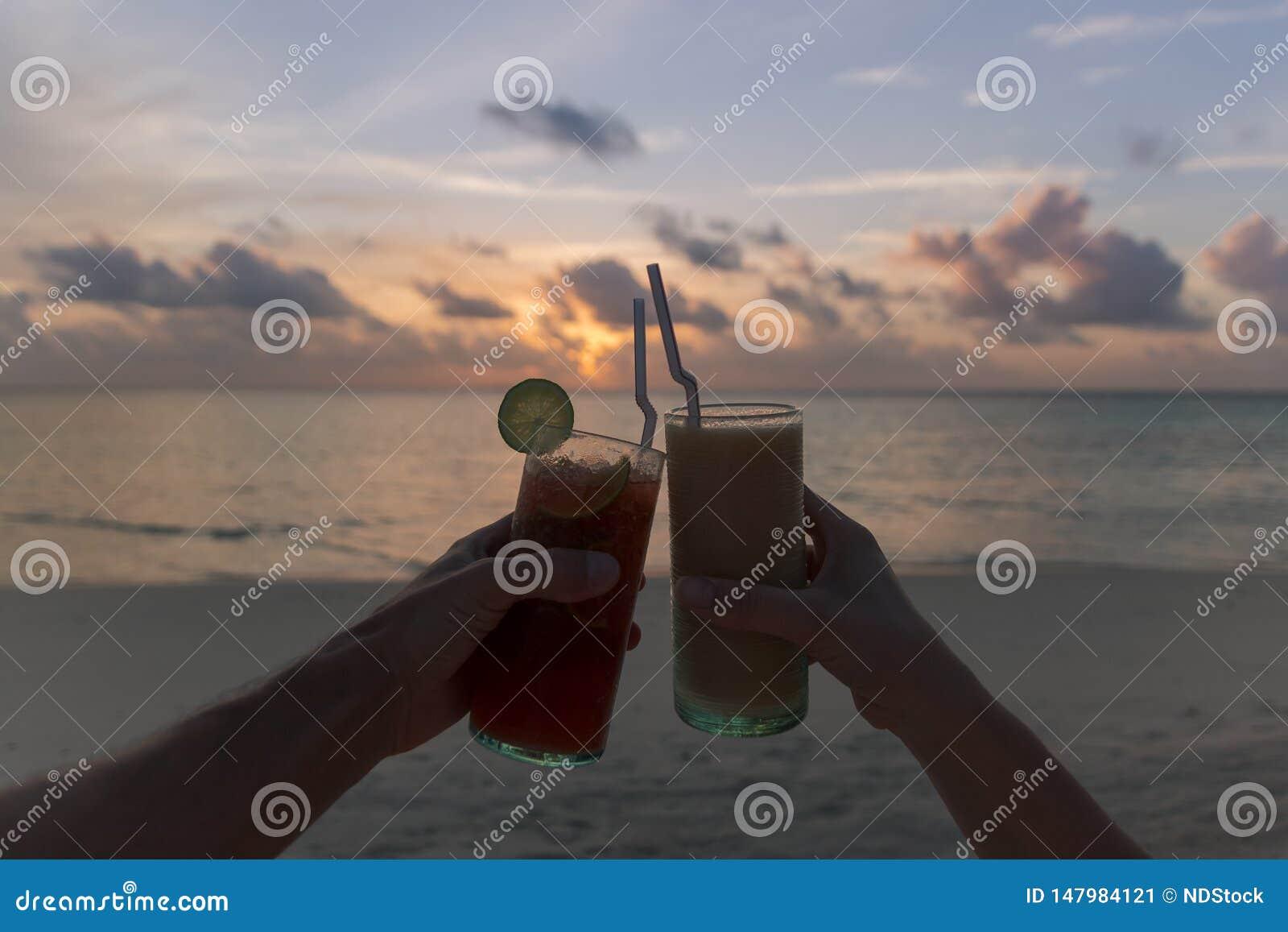 Två händer som klirrar coctailar under en solnedgång på stranden tropisk semester f?r ? Lycklig timme
