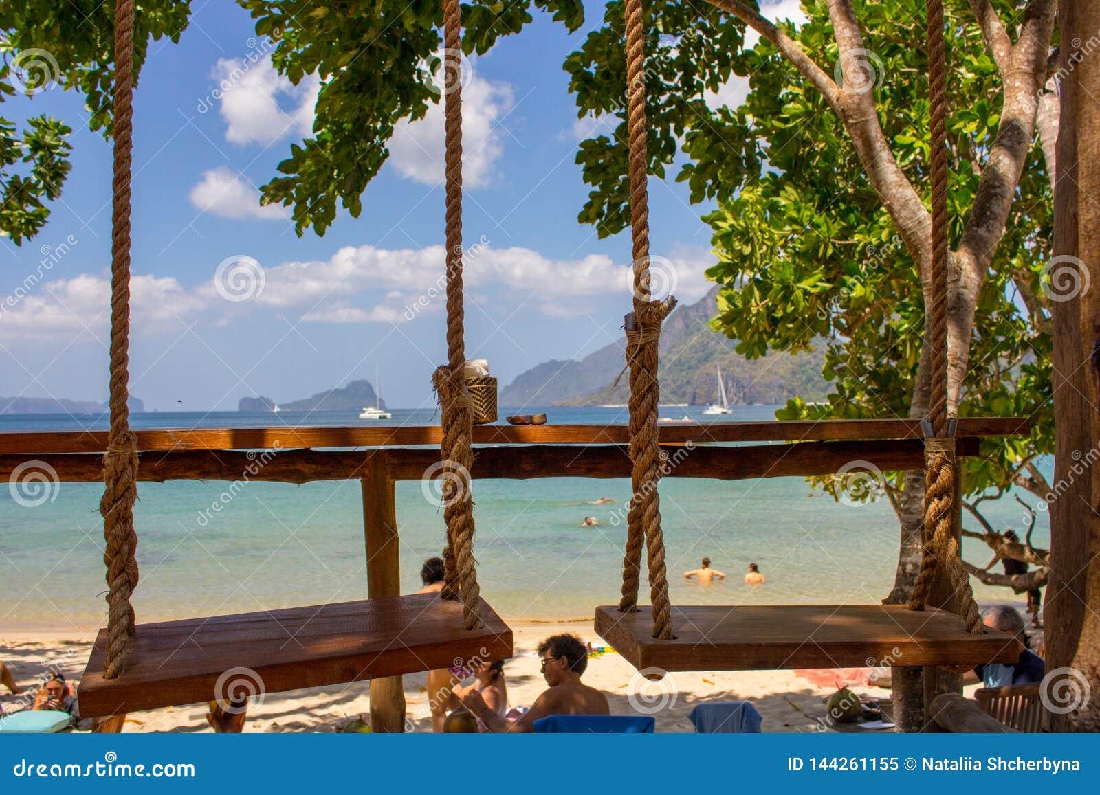 Två hängande gungor i utomhus- kafé på stranden Repgunga på den tropiska kusten Exotiskt loppbegrepp Semester i paradis