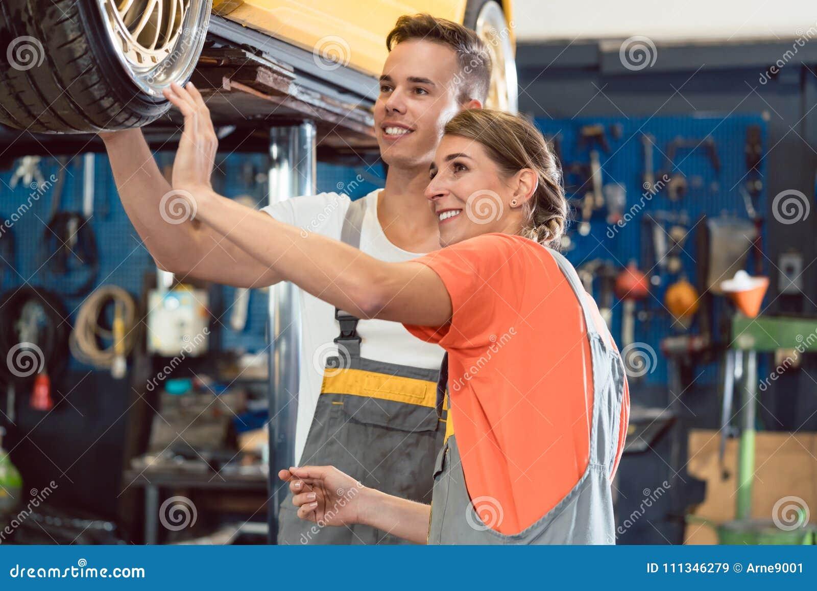 Två hängivna auto mekaniker som ler, medan kontrollera hjulen av en stämd bil