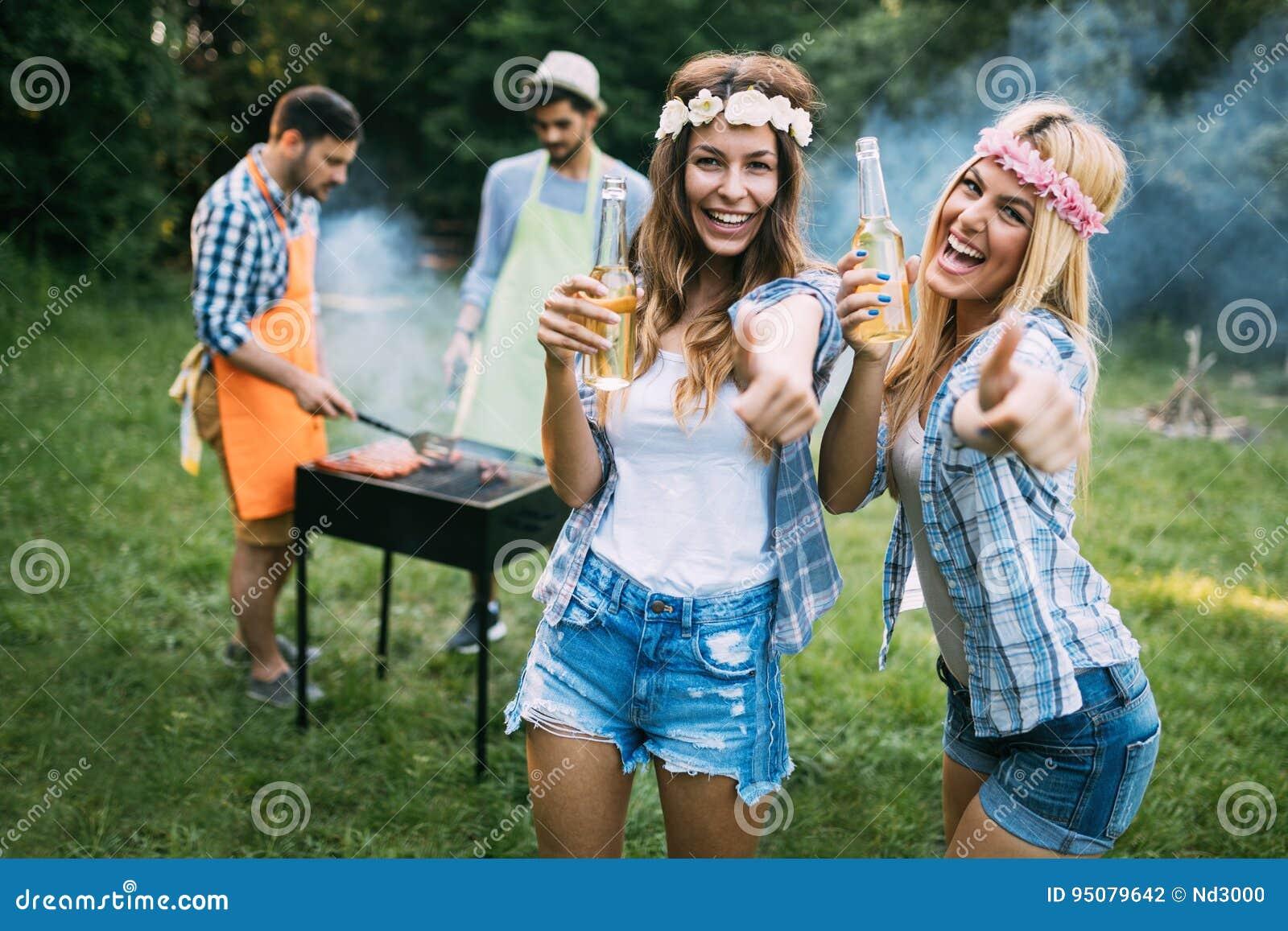Två härliga kvinnor som har gyckel, medan vänta på grillfesten