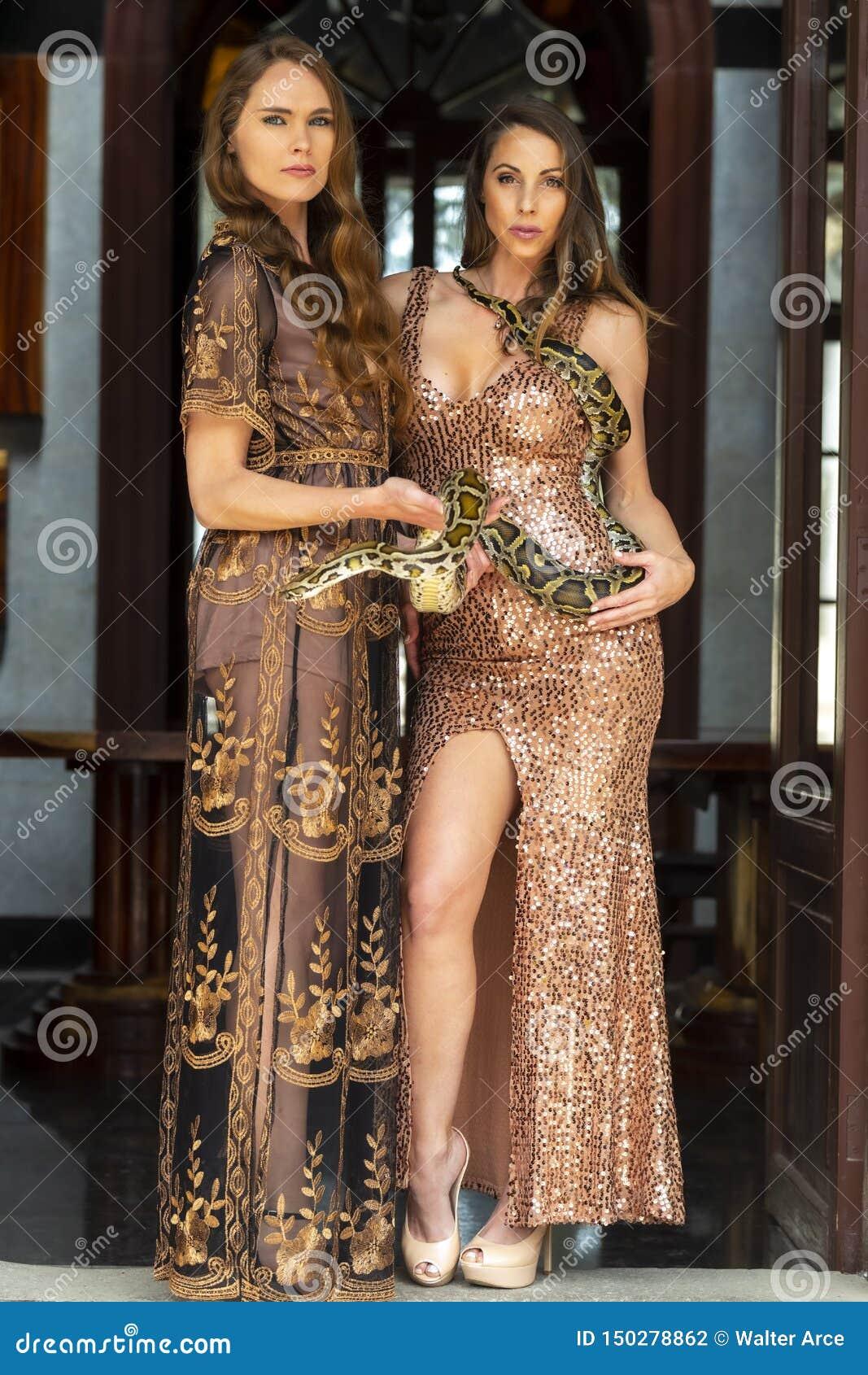 Två härliga latinamerikanska brunettmodeller poserar med en orm för BoaConstrictor runt om hennes kropp