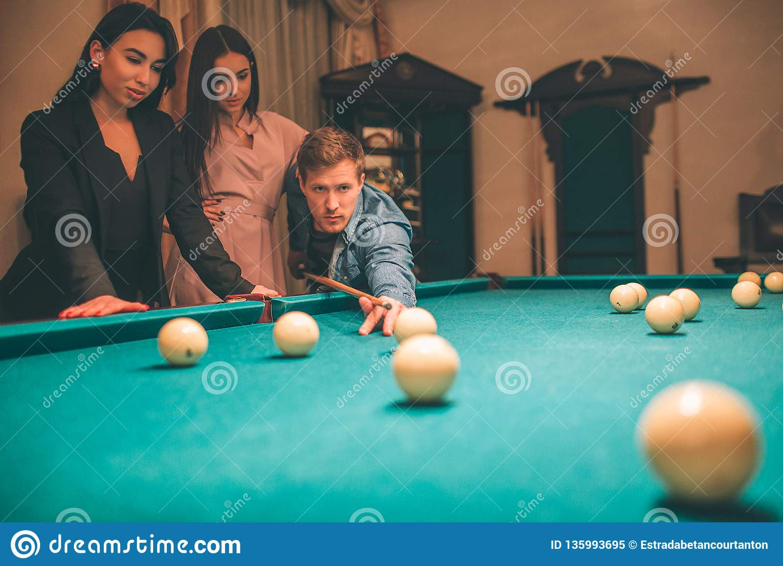 Två härliga modeller håller ögonen på hur rödhårig manmannen som plying billiard Han står, i vinkelposition med billiardstickrepl