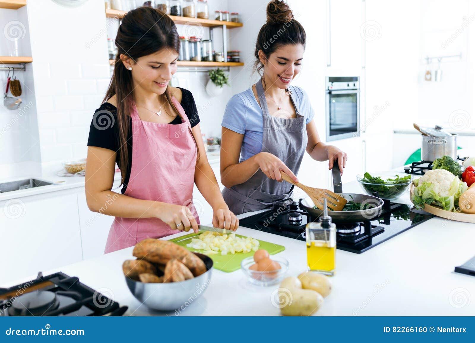 Två härliga unga kvinnor som lagar mat chards och skivar potatisar i köket