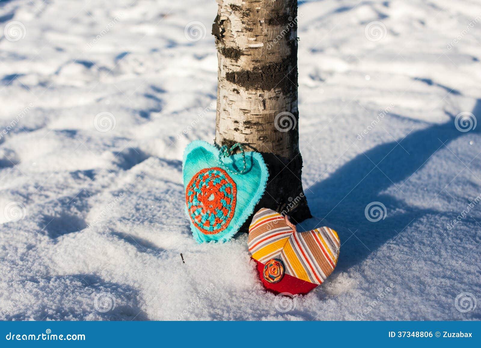 Två   handgjorda hjärtor på en snöbakgrund