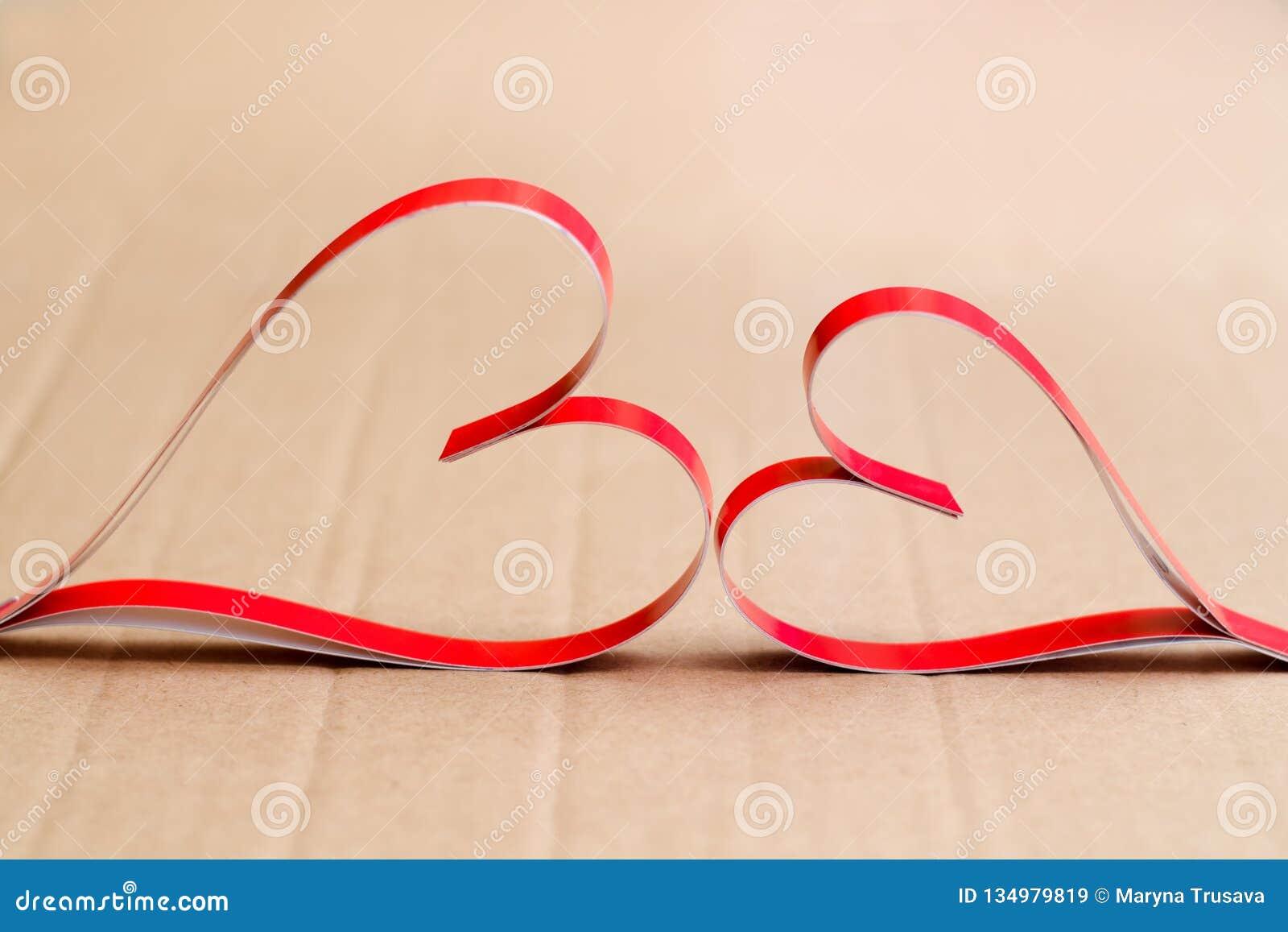 Två hemlagade pappers- röda hjärtor på en beige pappbakgrund, symbolet av valentin dag