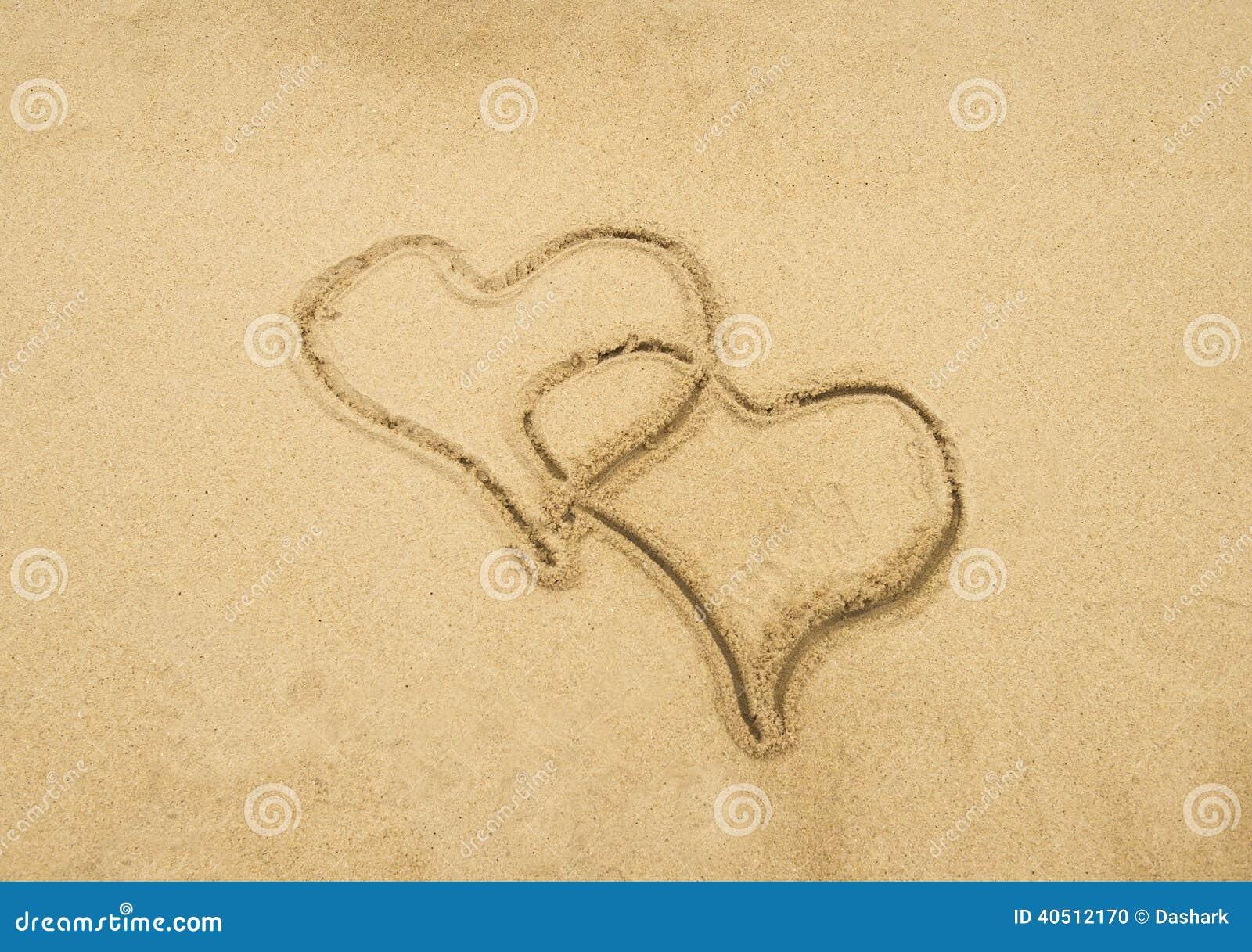 Två hjärtor som tecknas i strand