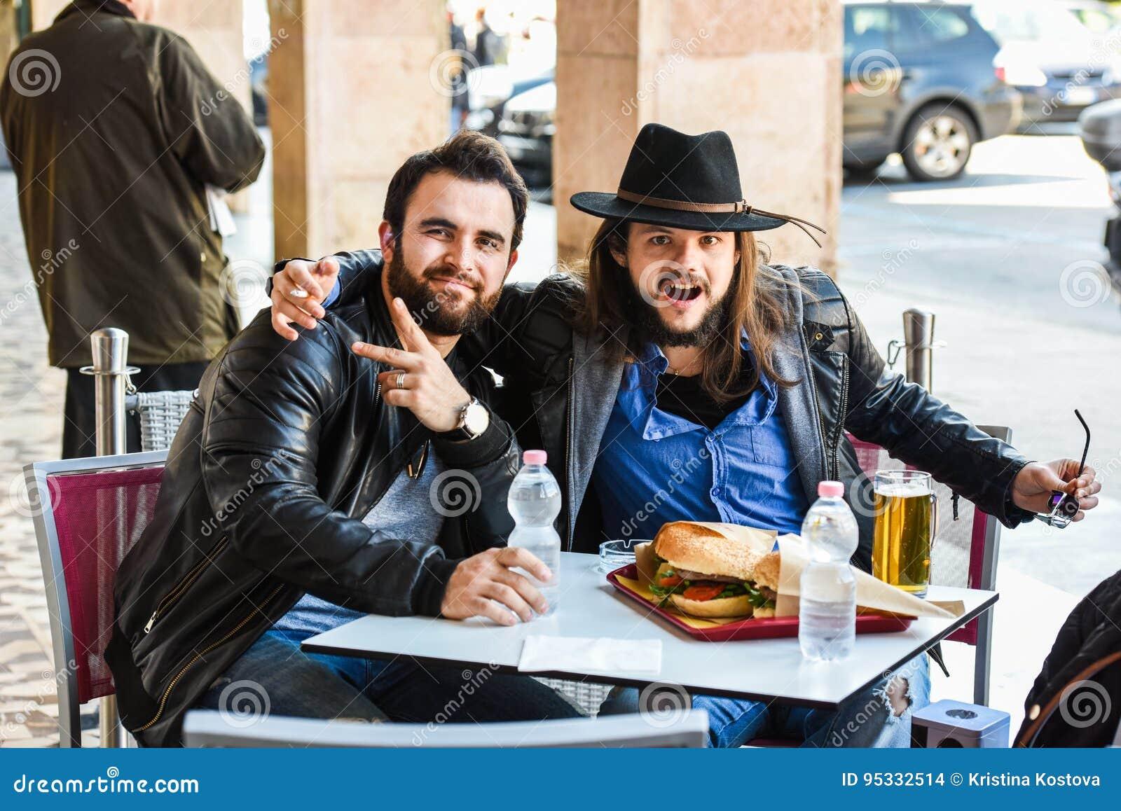 Två hungriga vänner/turister äter utanför i det öppet