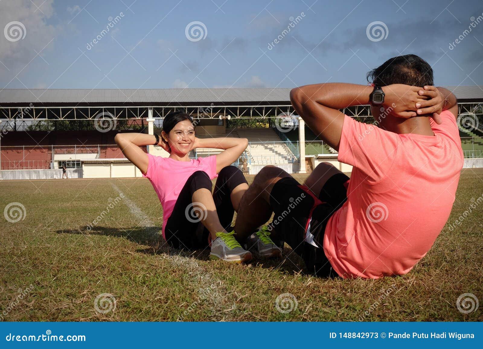 Tv? idrottsm?n knastrar tillsammans p? en solig dag som b?r orange och rosa skjortor De ?var p? gr?set av en fotboll