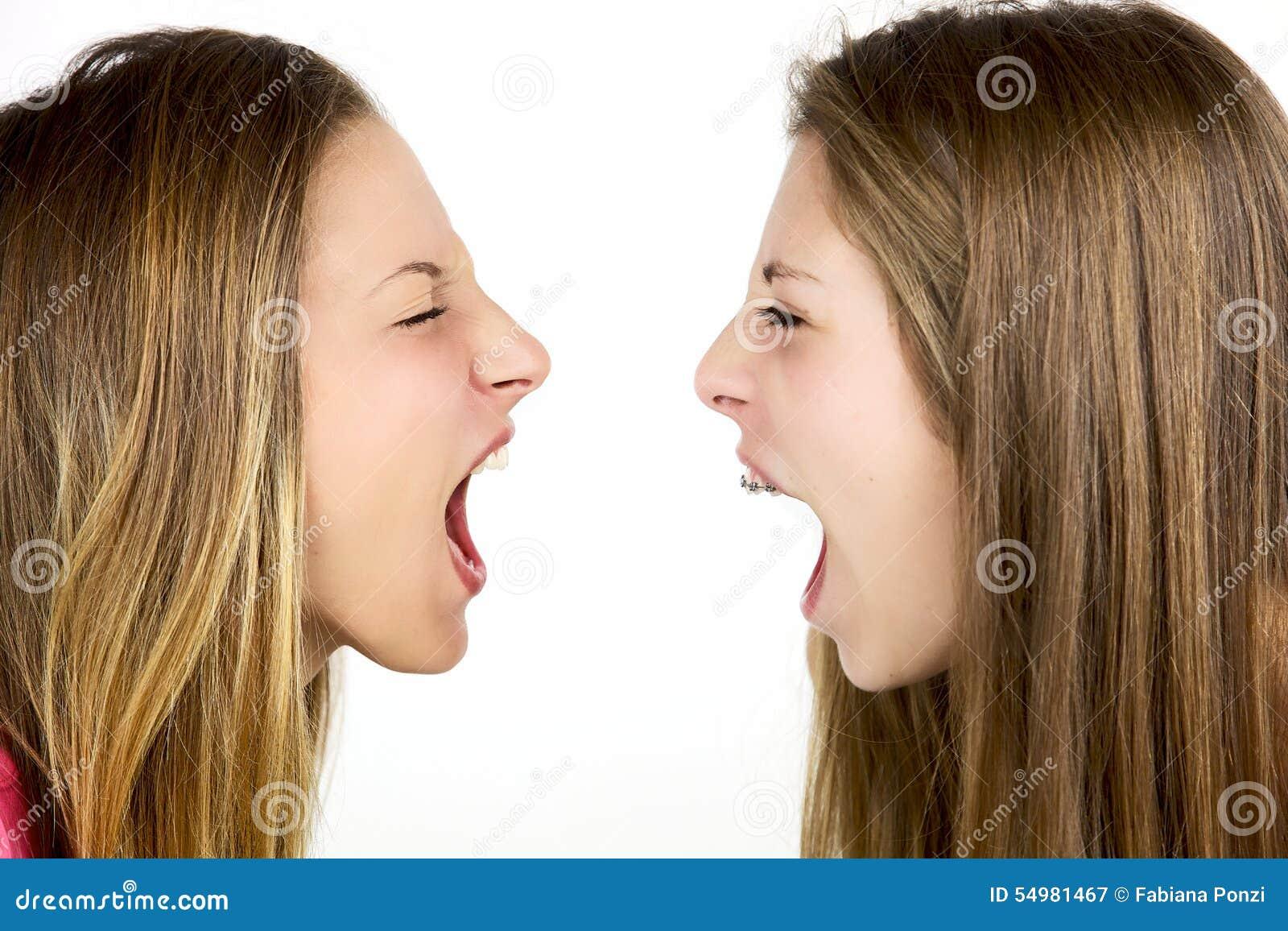 Två ilskna blonda flickor som skriker på de, isolerade