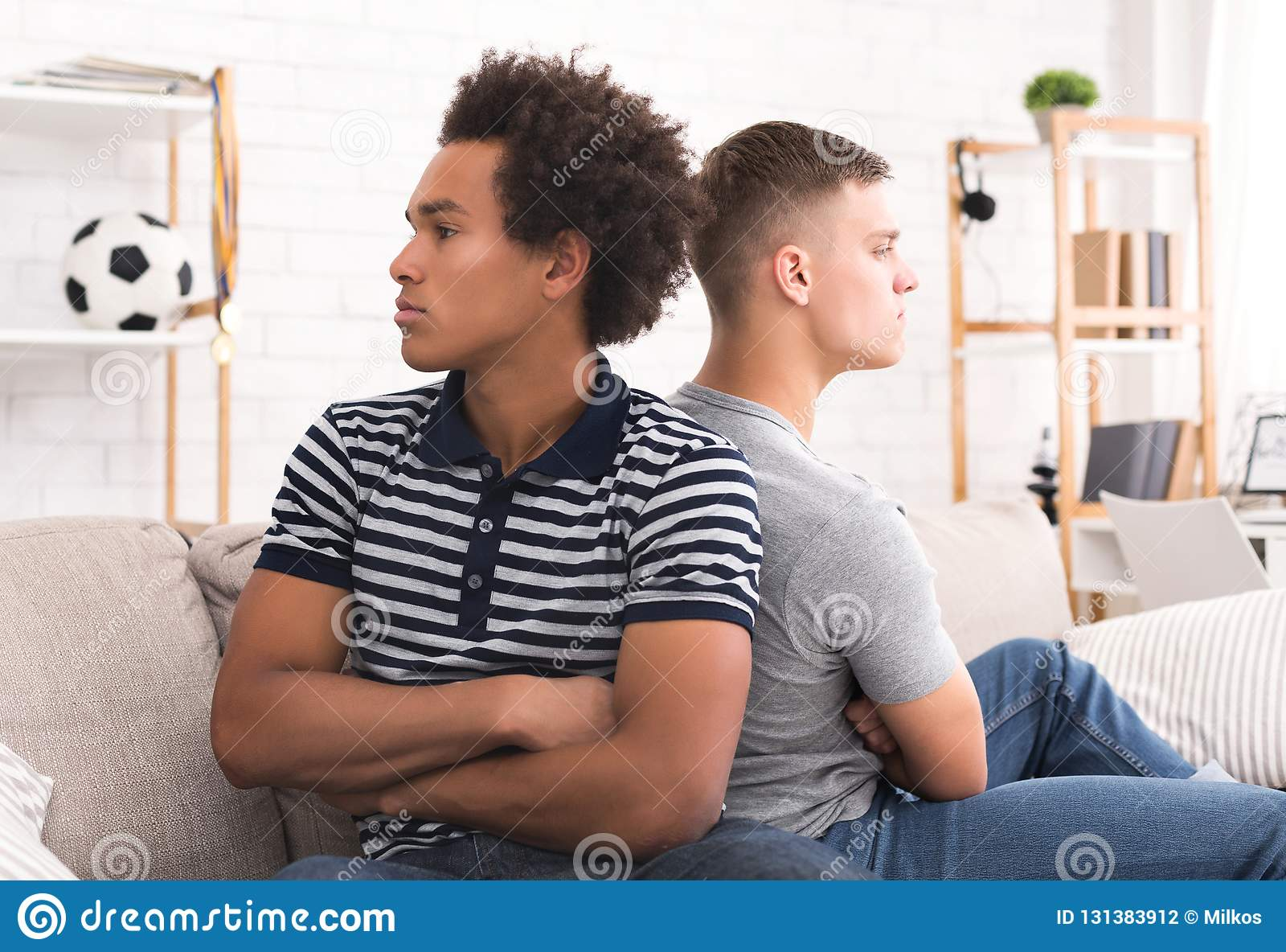 Två ilskna rumskamrater som tillbaka till varandra sitter