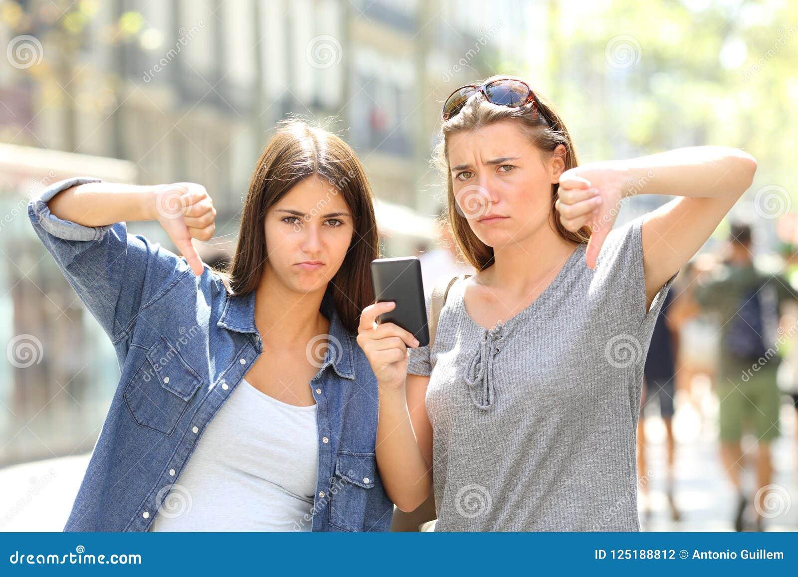 Två ilskna vänner som rymmer en telefon med tummar ner