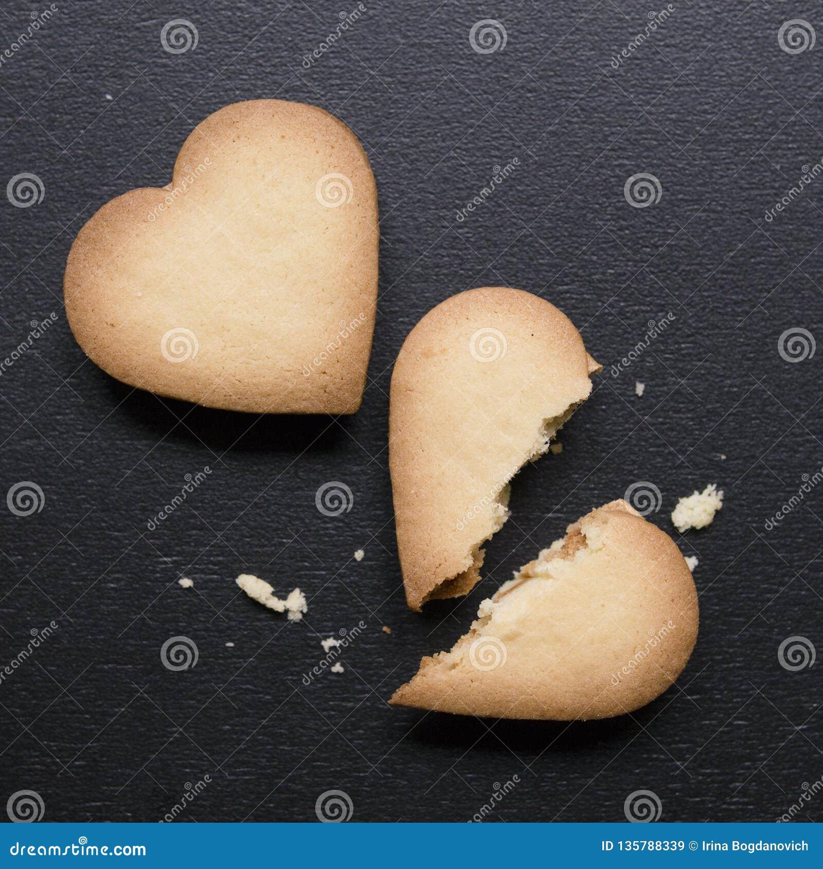 Två kakor i formen av hjärta, ett av dem är brutna på svart bakgrund Knäckt hjärta formade kakan som begrepp av upplösningen