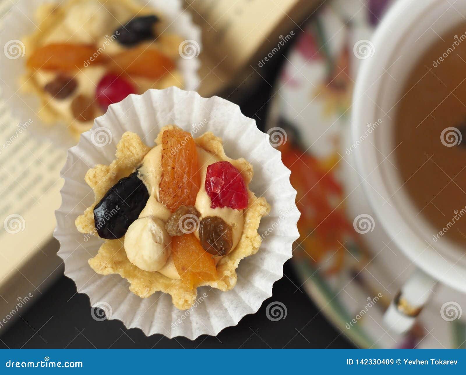 Två kakor med smörkräm och frukt nära en kopp te på den öppnade boken