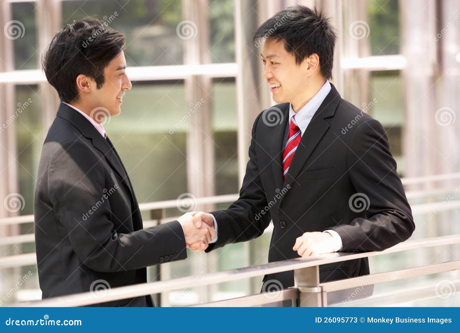 Två kinesiska affärsmän som upprör händer