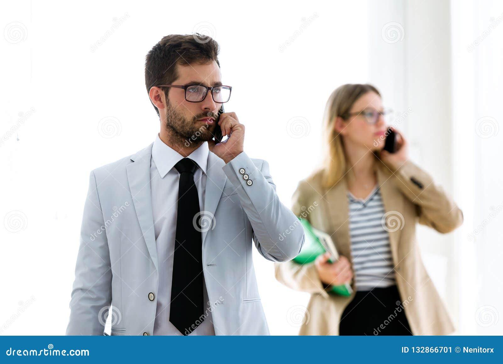 Två koncentrerade unga affärspartners som talar med deras smartphones i ett hall av dem företaget
