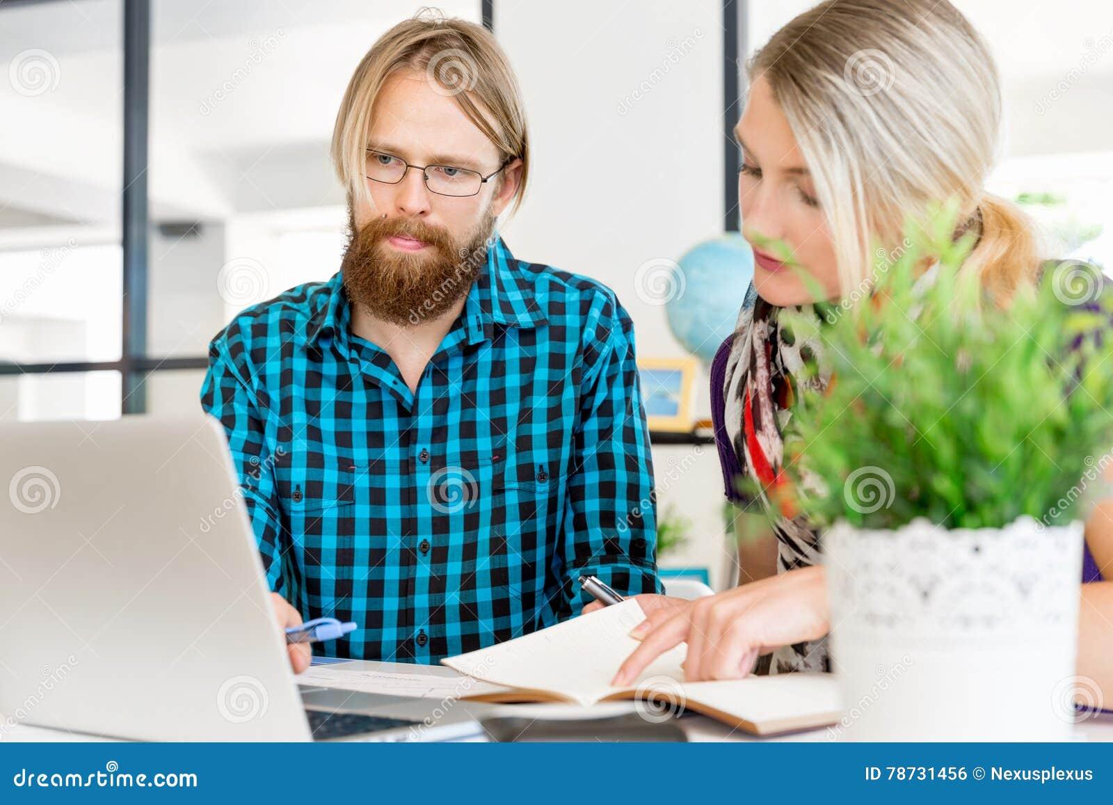 Två kontorsarbetare på skrivbordet
