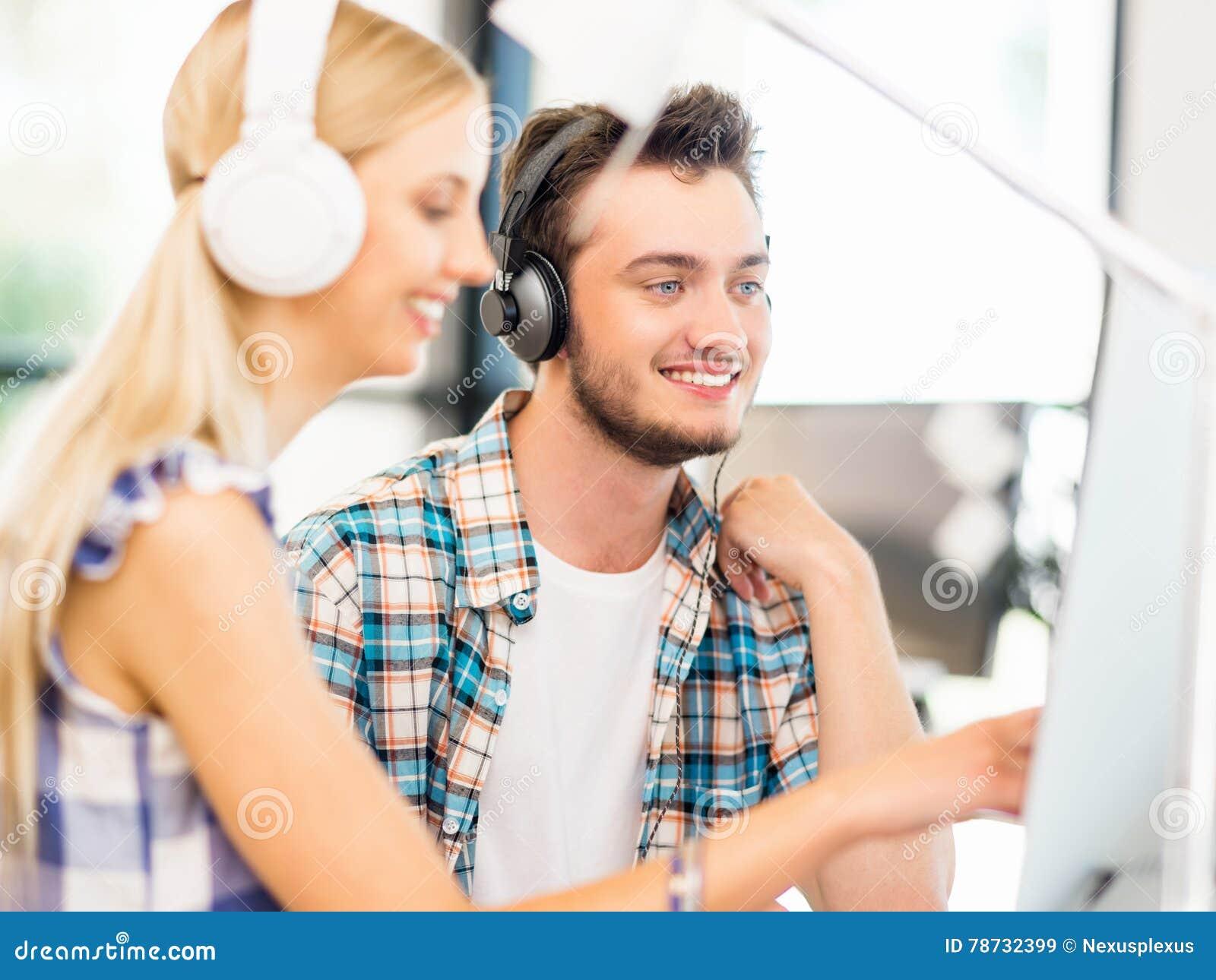Två kontorsarbetare på skrivbordet med hörlurar