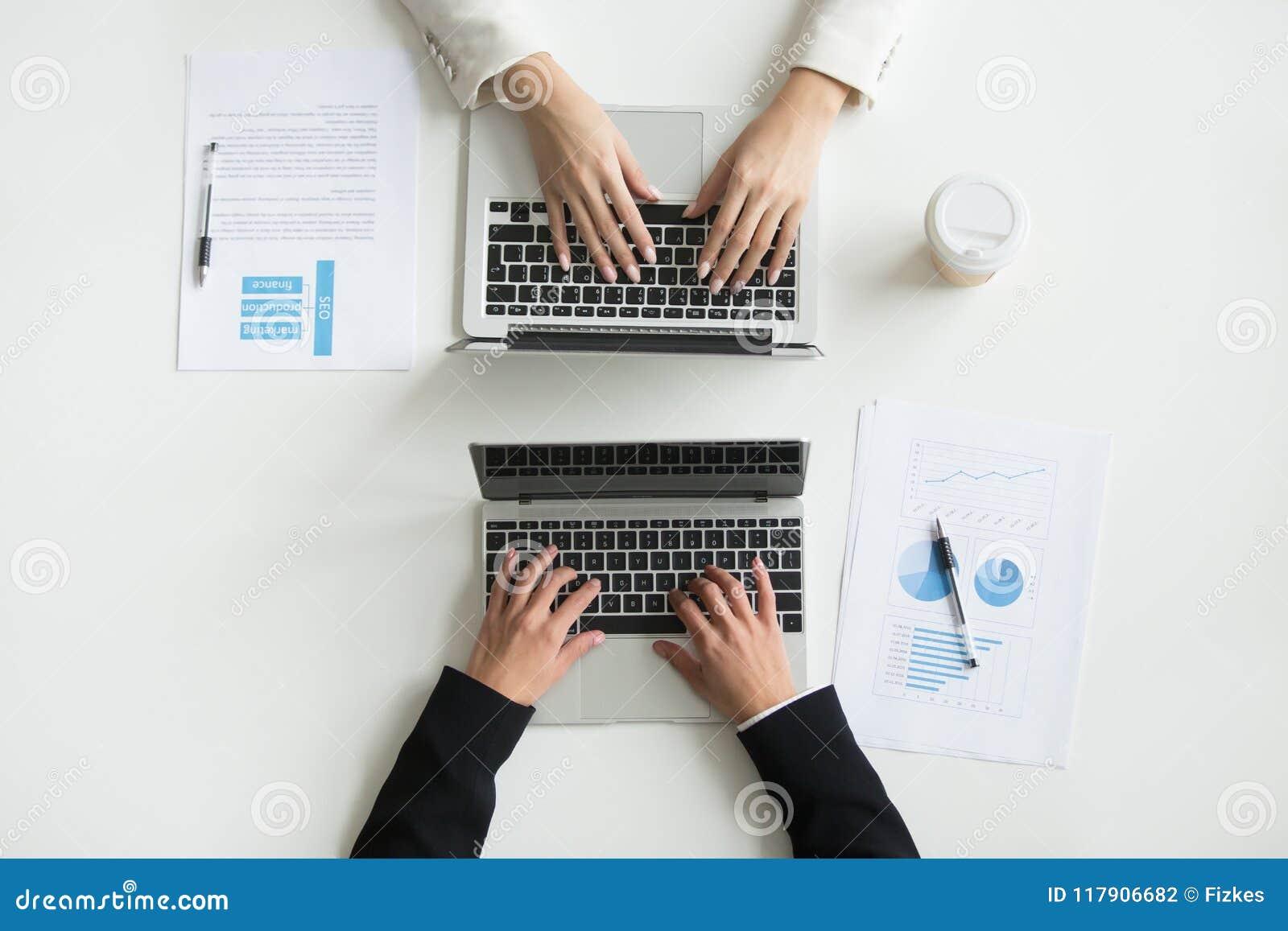 Två kontorsarbetare som skriver på bärbara datorer, övre sikt för bästa slut