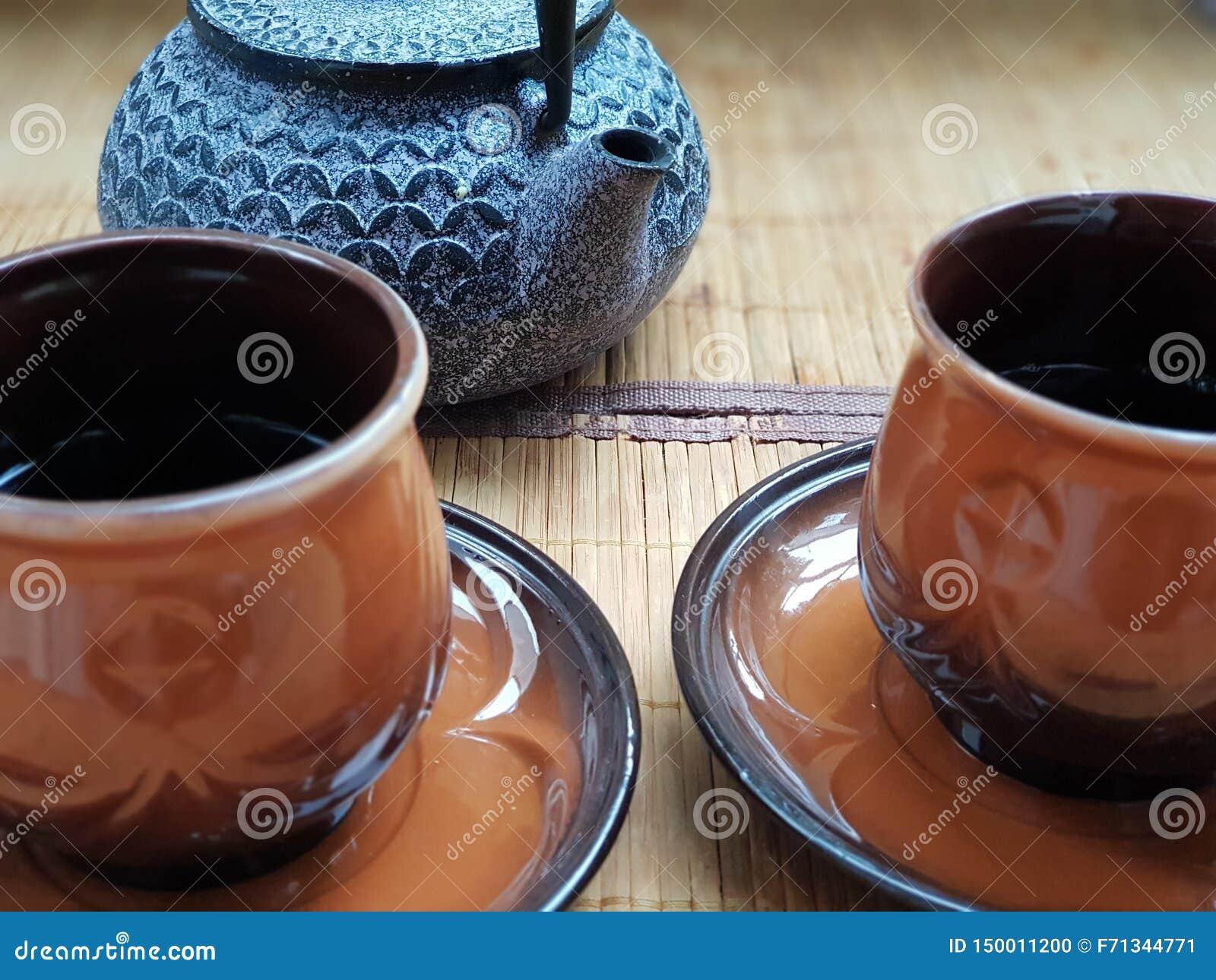 Två koppar av förnyande te med en kokkärl