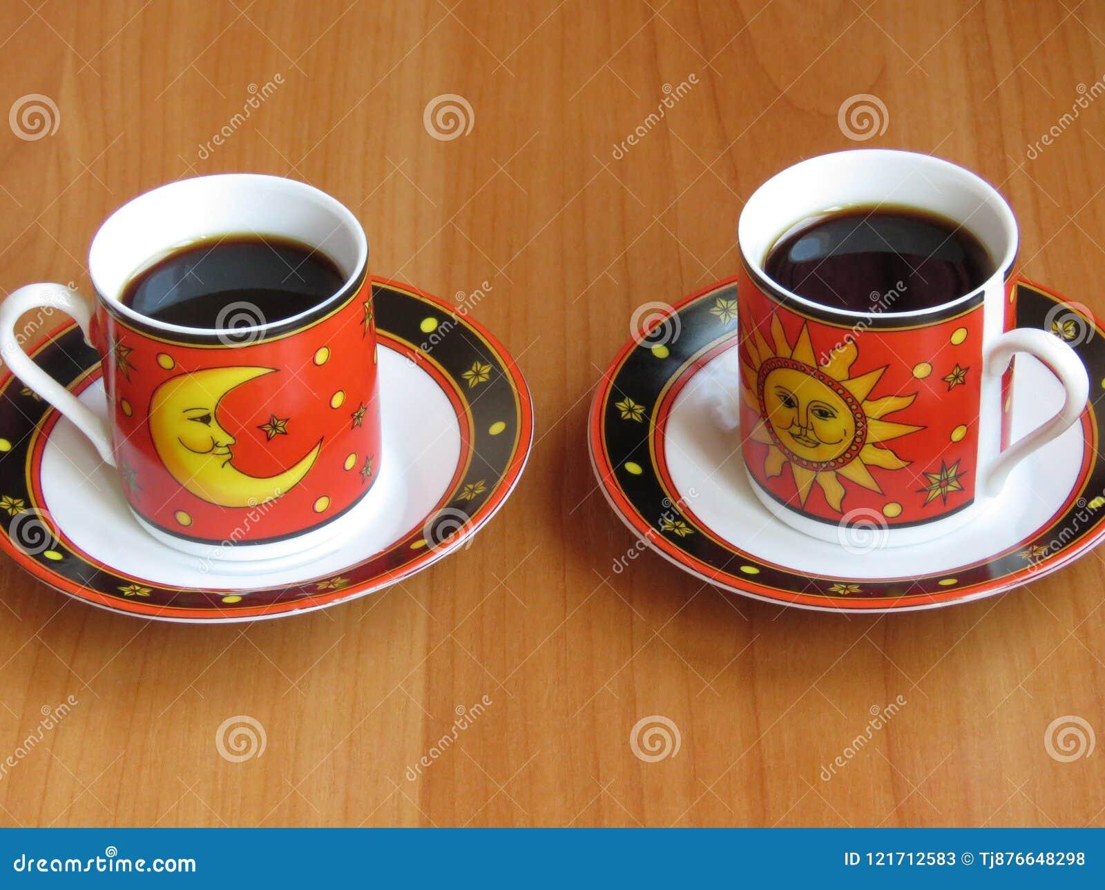 Två koppar av mörkt kaffe i rött med måne- och solbeståndsdelar