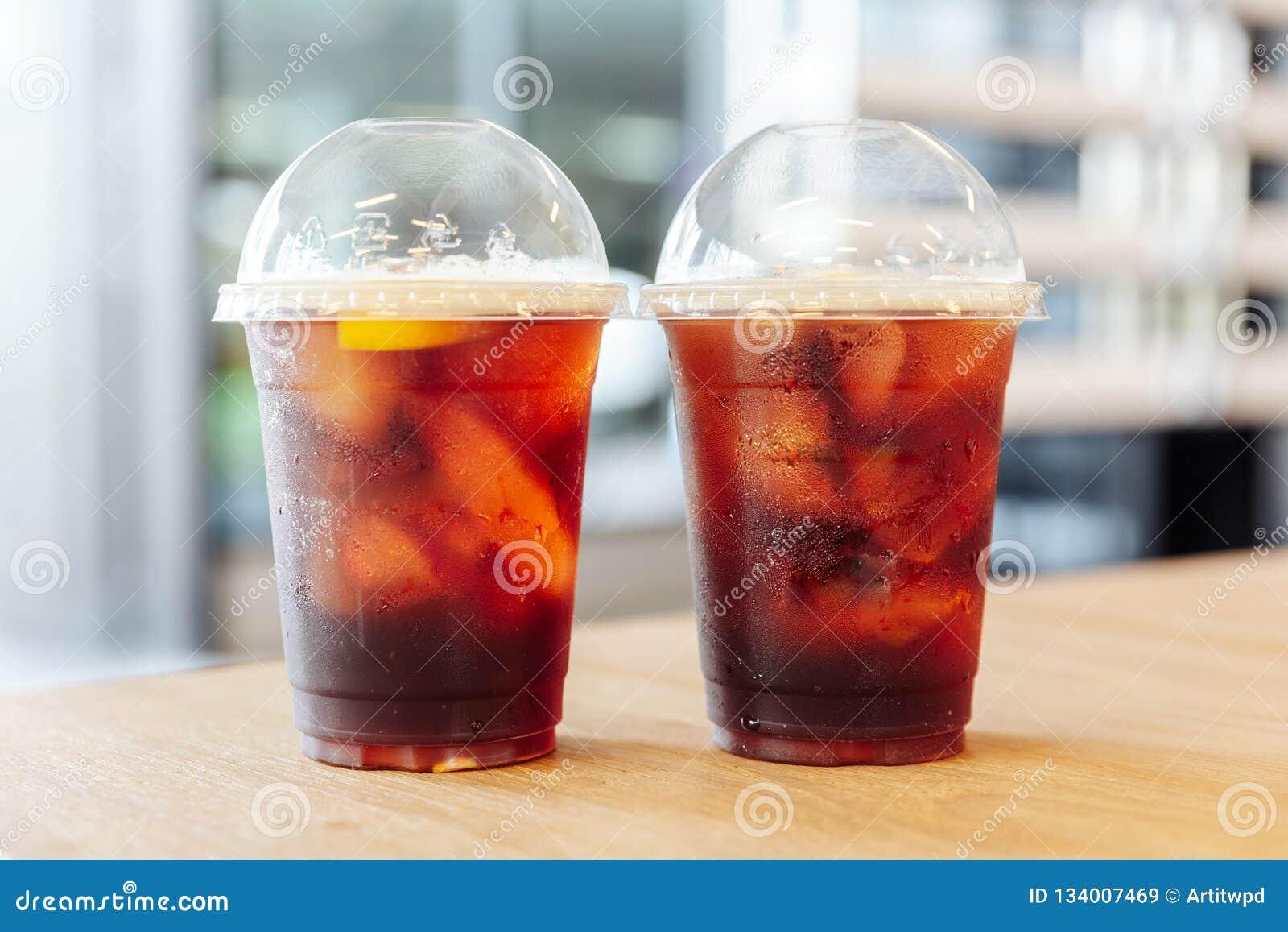 Två koppar av med is nitro kallt brygdkaffe med citronen på trätabellen med suddighetsbakgrund