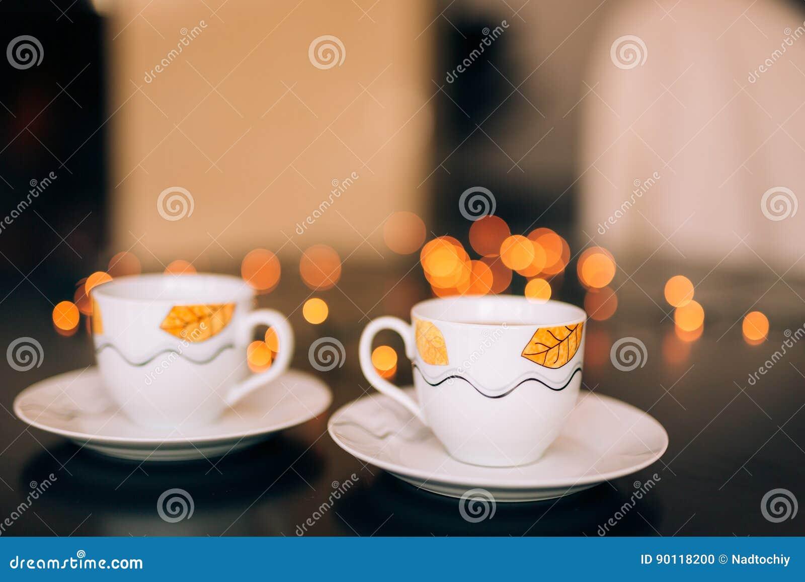Två koppar kaffe på tabellen på bakgrundsbokeh
