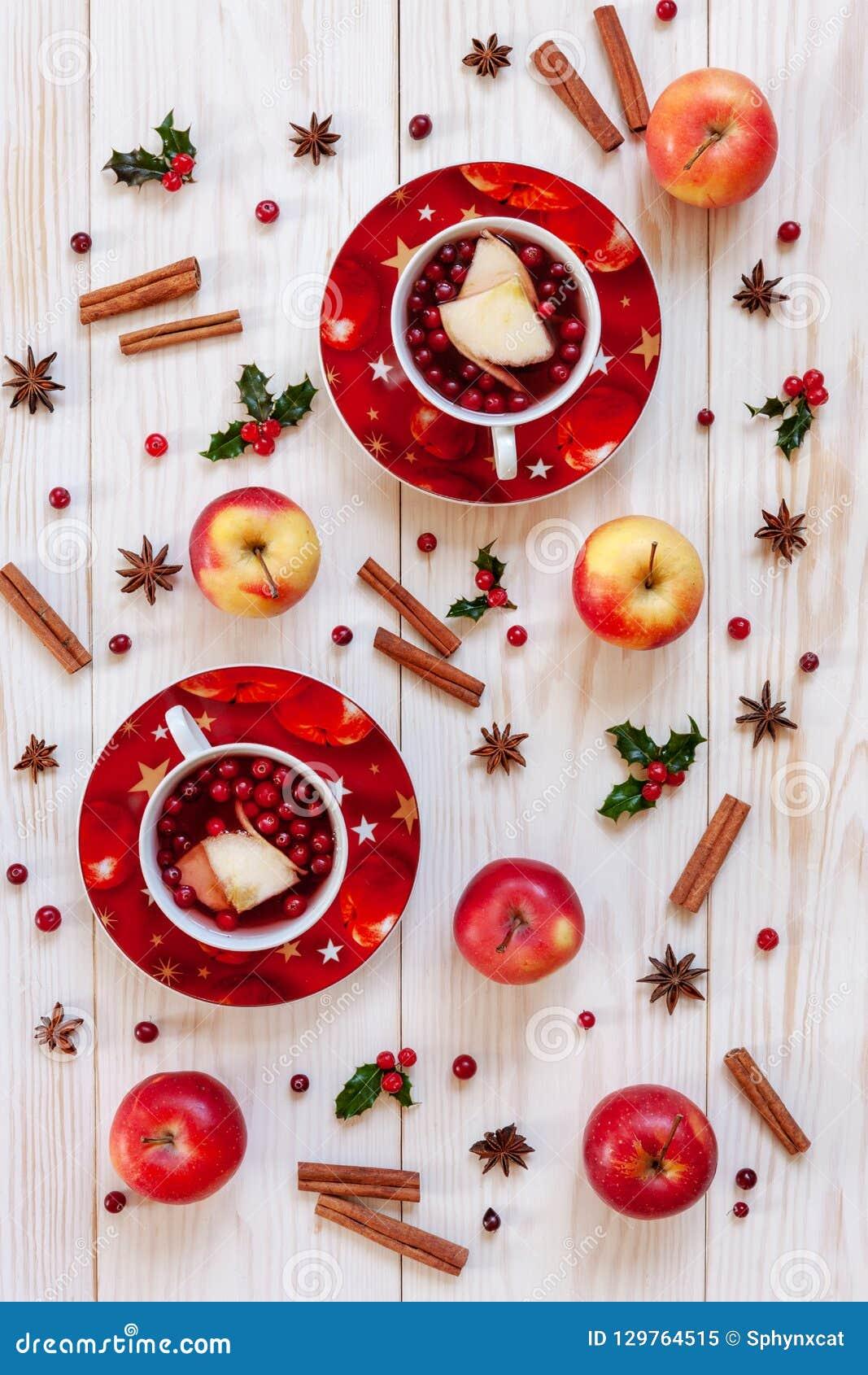 Två koppar med den varma julfruktdrinken med kryddor och bär